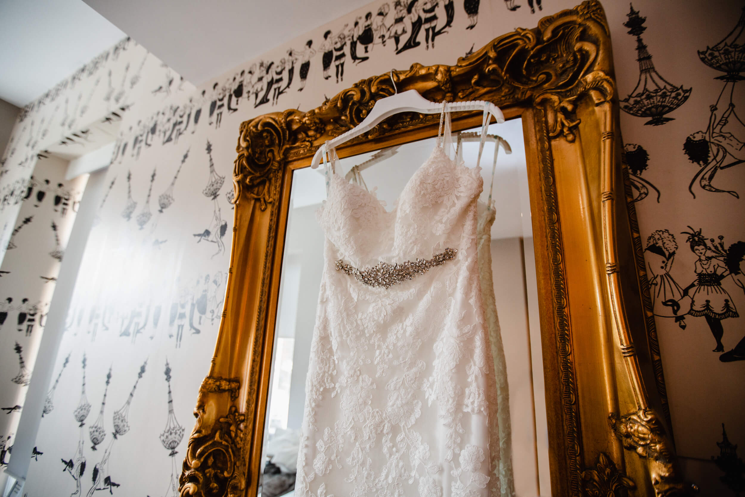 close up detail photograph of wedding dress hung on mirror