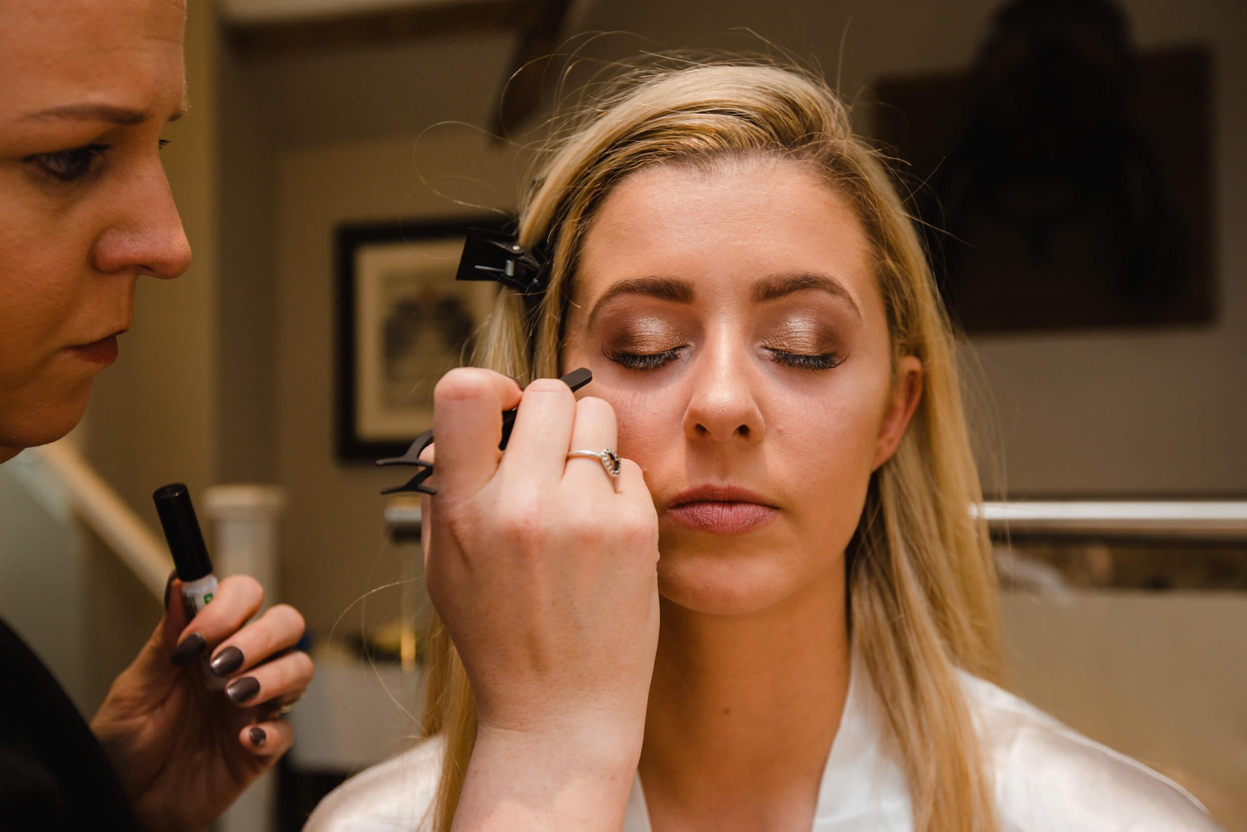 close up macro lens photograph of bride having mascara make up applied