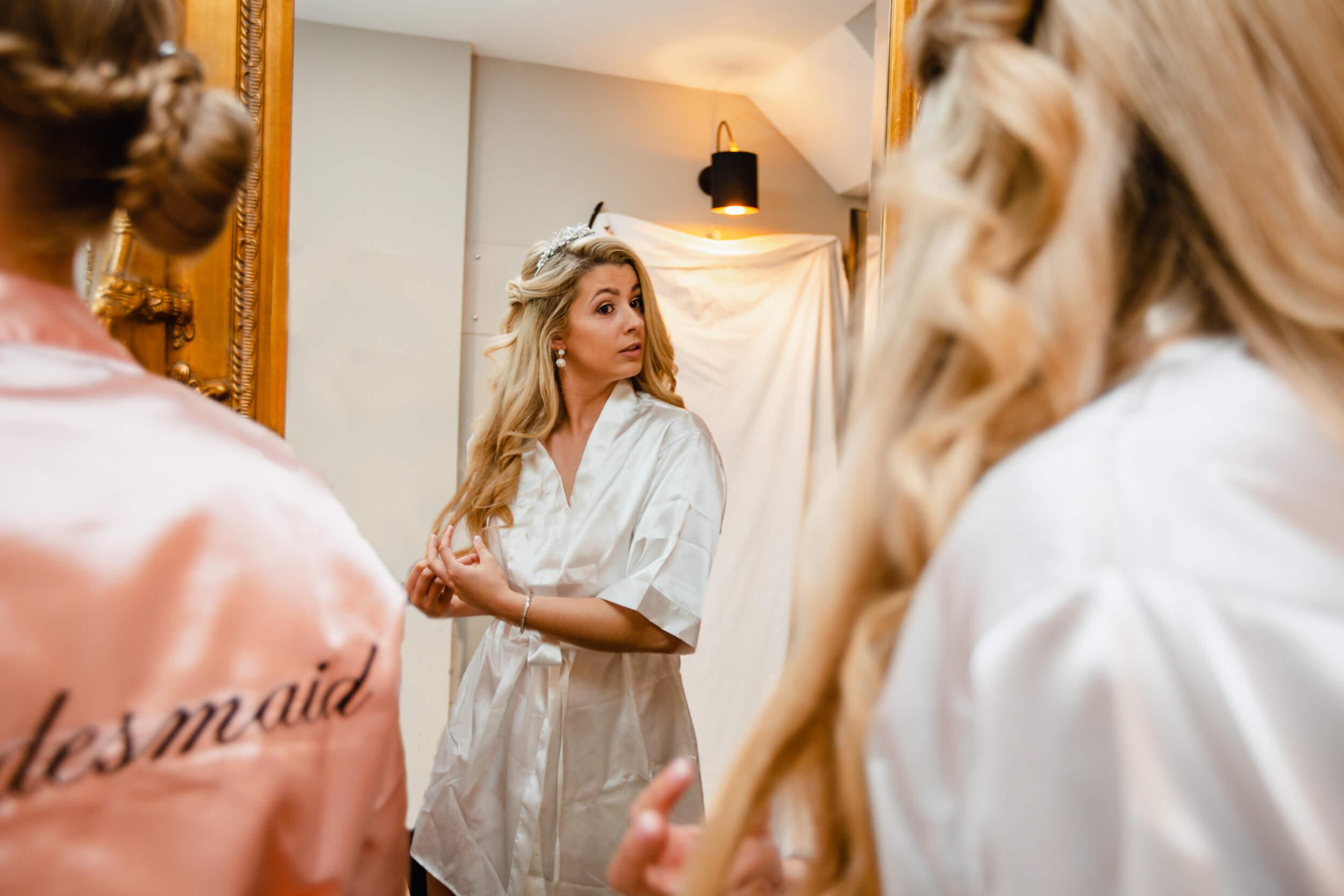bride looking in mirror while stroking hair