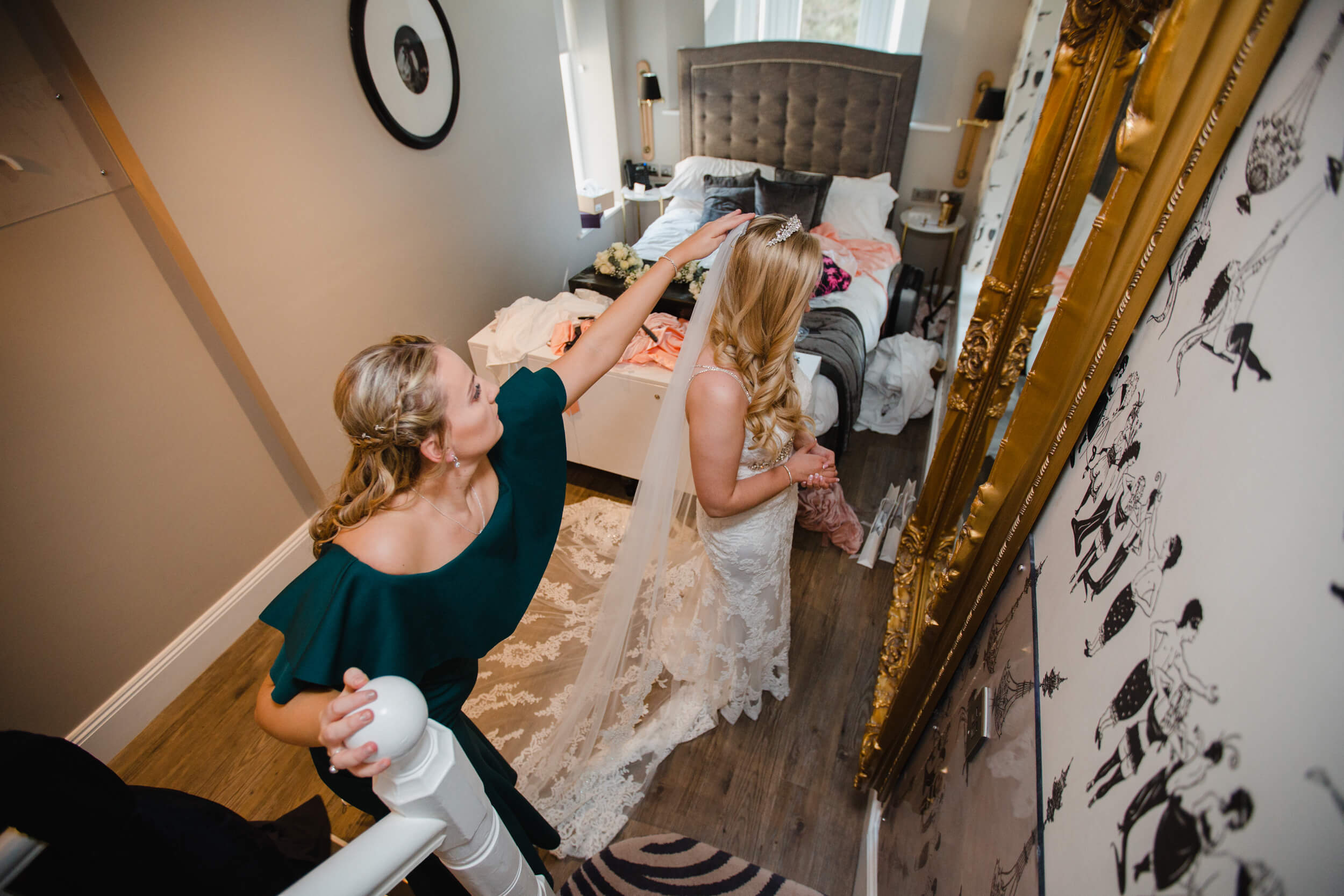 bridesmaid attaching veil to brides headpiece tiara during preparation