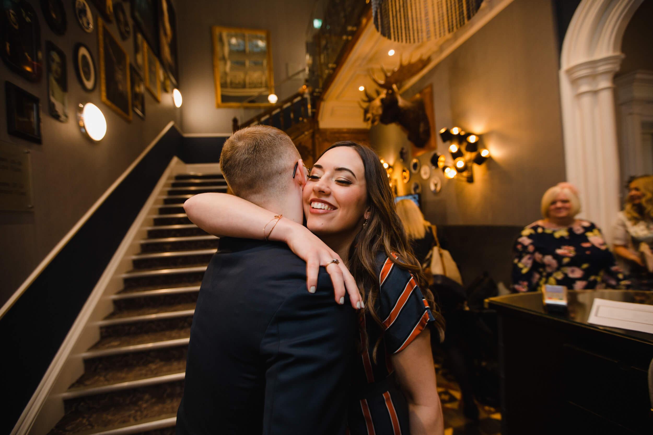 wedding guest sharing hug with groom before wedding ceremony