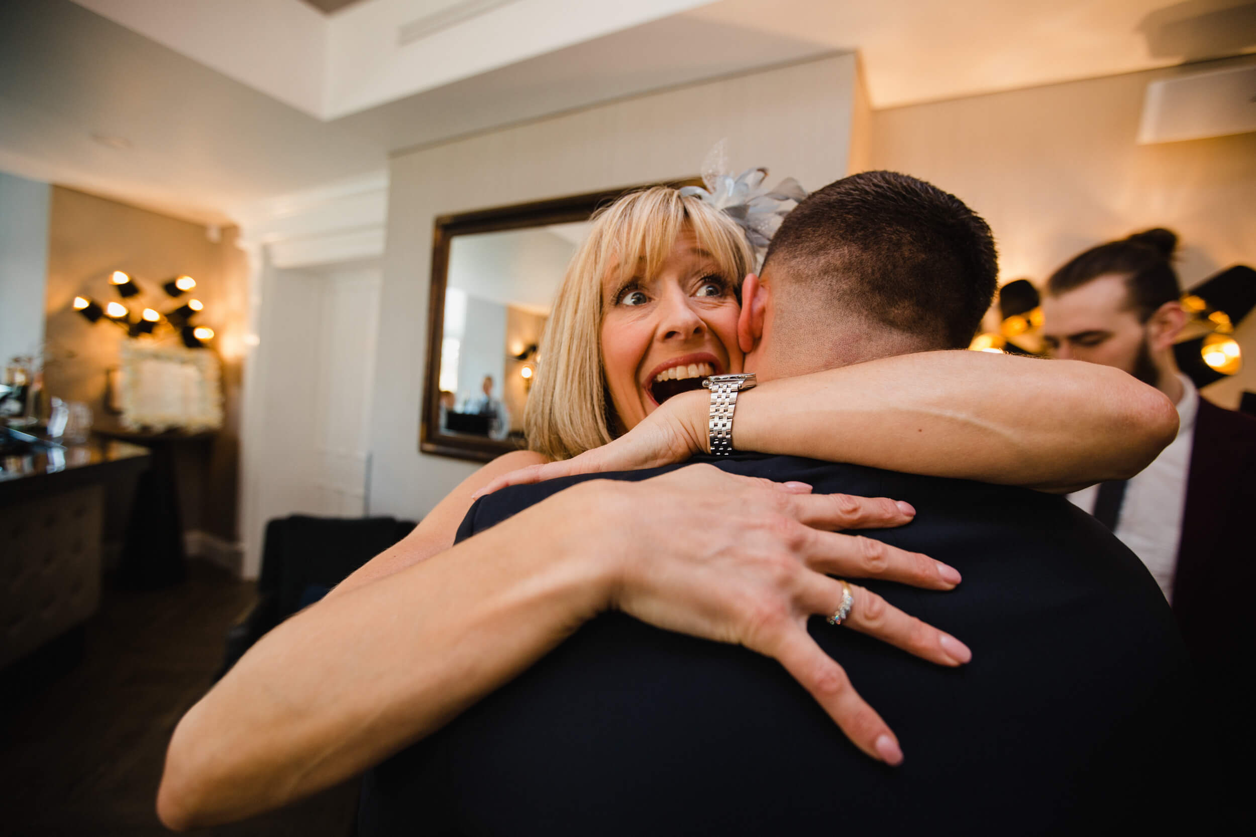 mother of groom sharing a hug with son before wedding processional commences