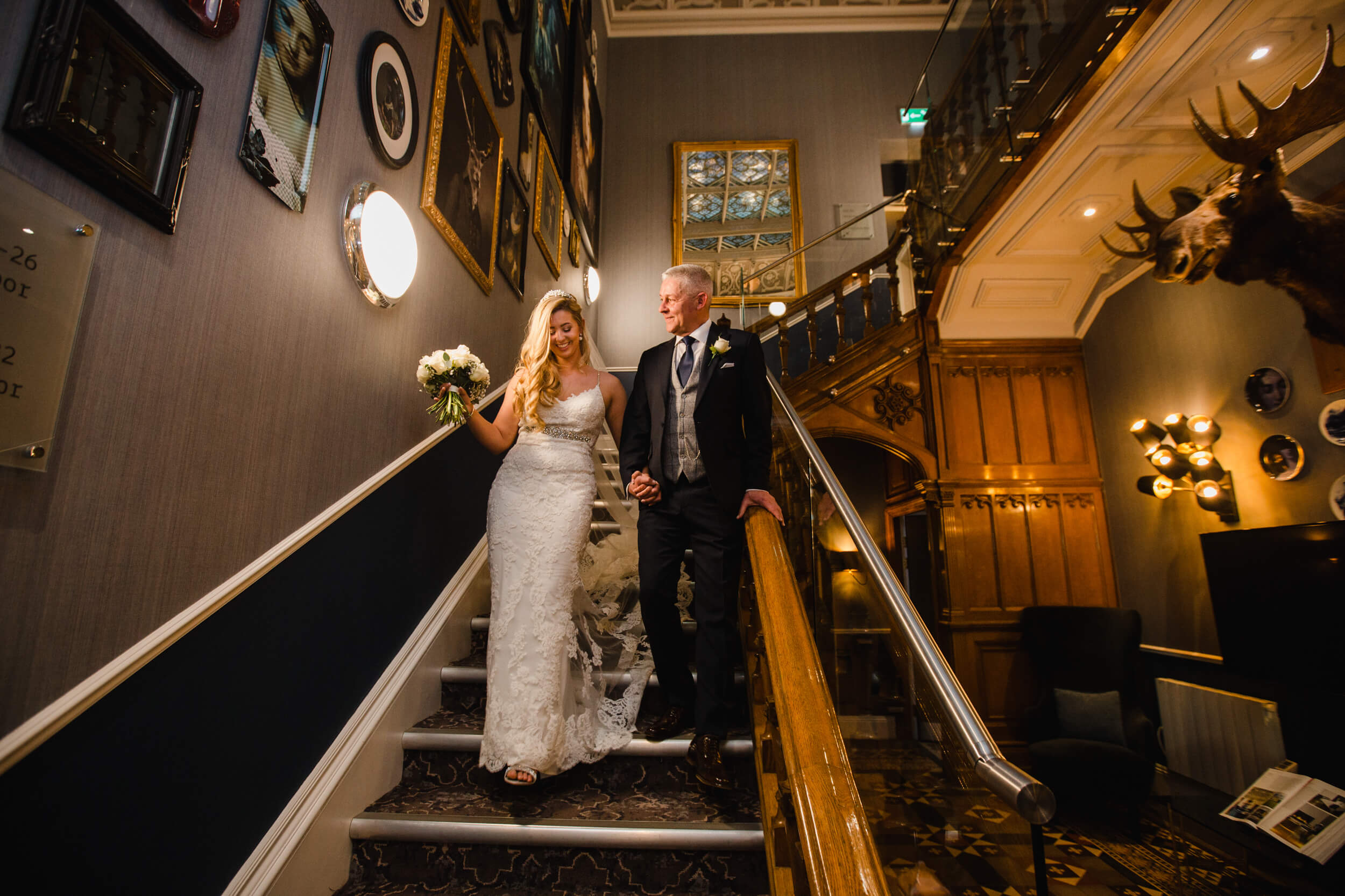 close up of father and bride walking down staircase into hallway