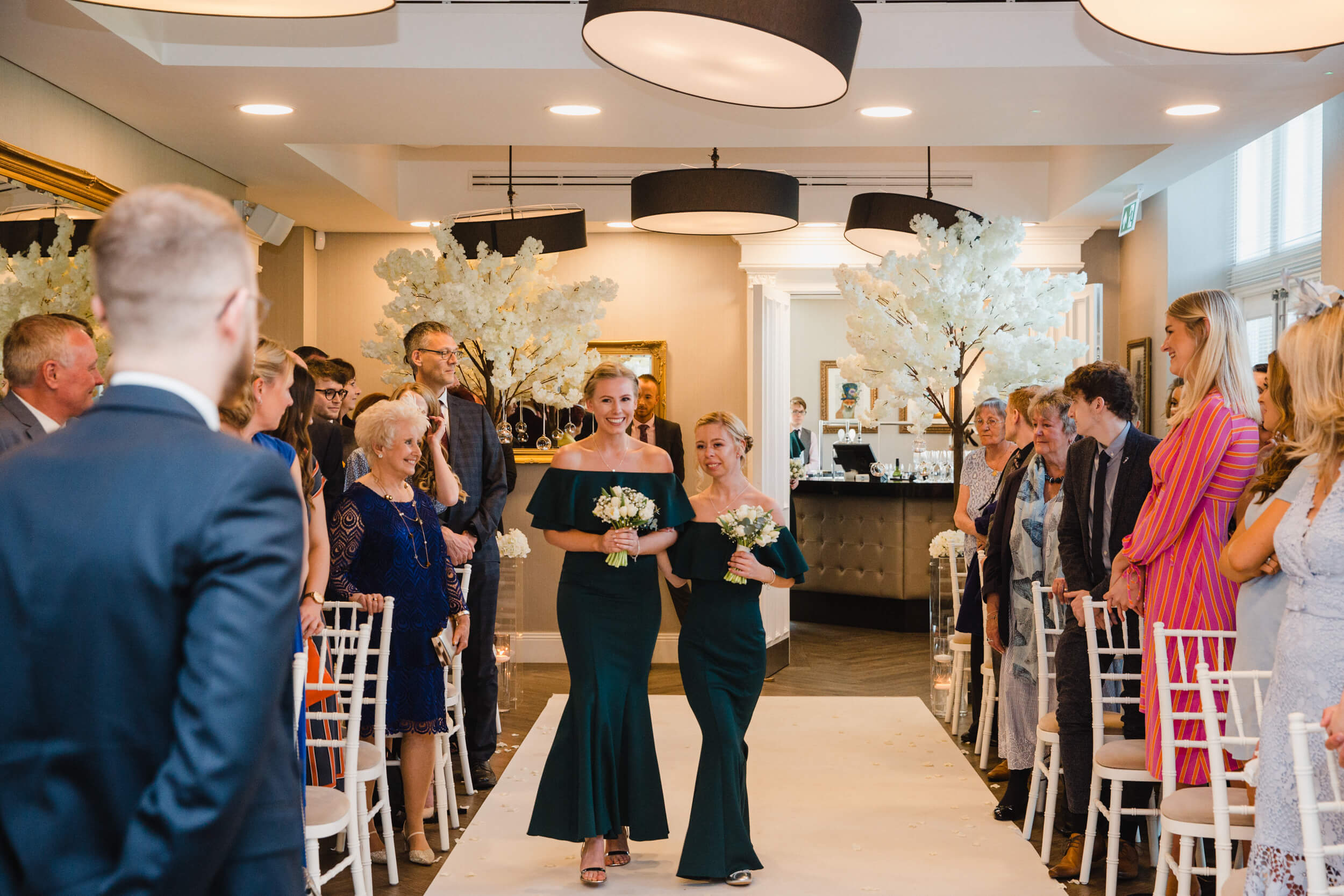 bridesmaids holding bouquets walking down aisle to begin wedding ceremony processional with groom in foreground