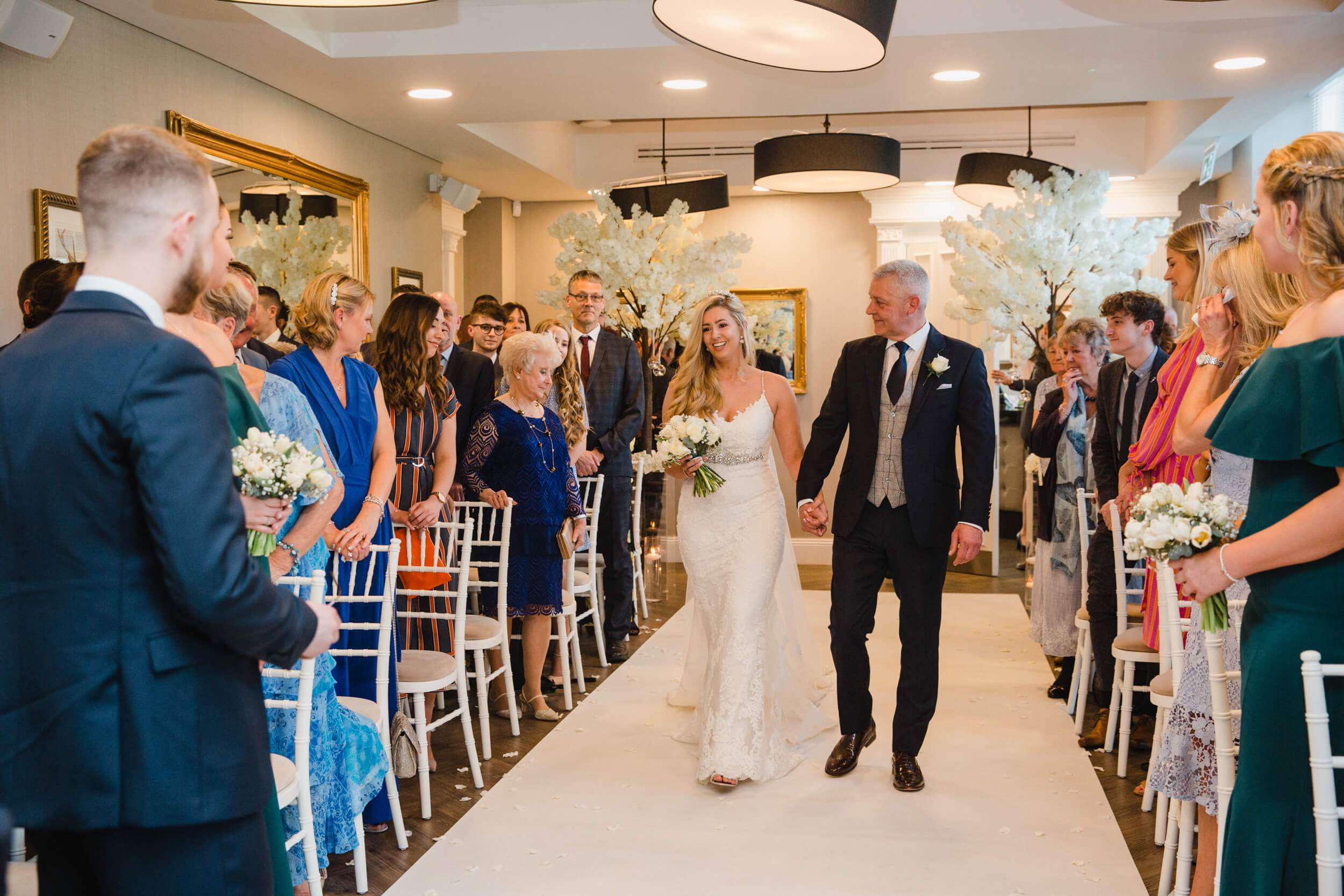 bride and father walk down aisle together surrounded by wedding party