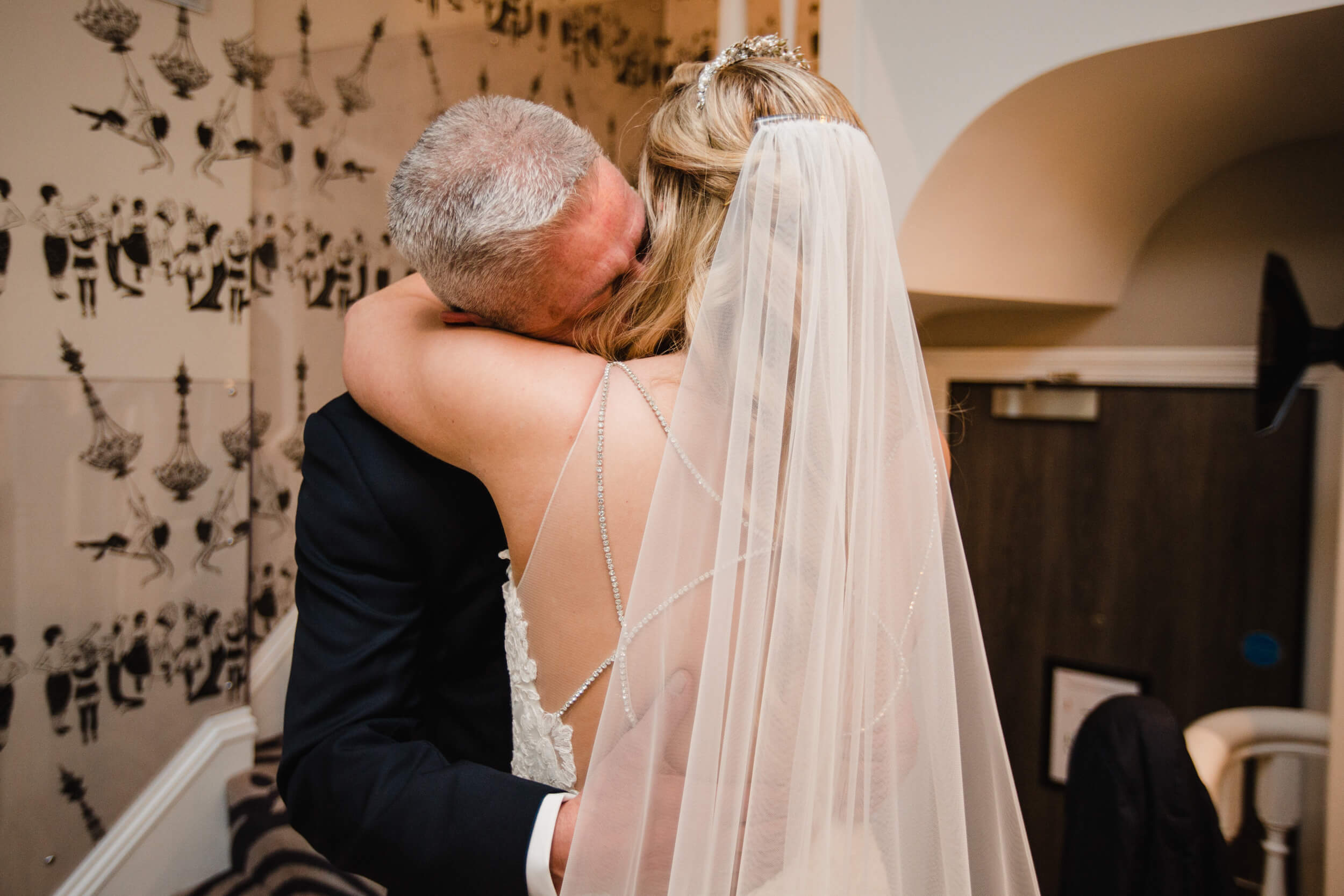 close intimate photograph of father hugging bride before wedding ceremony