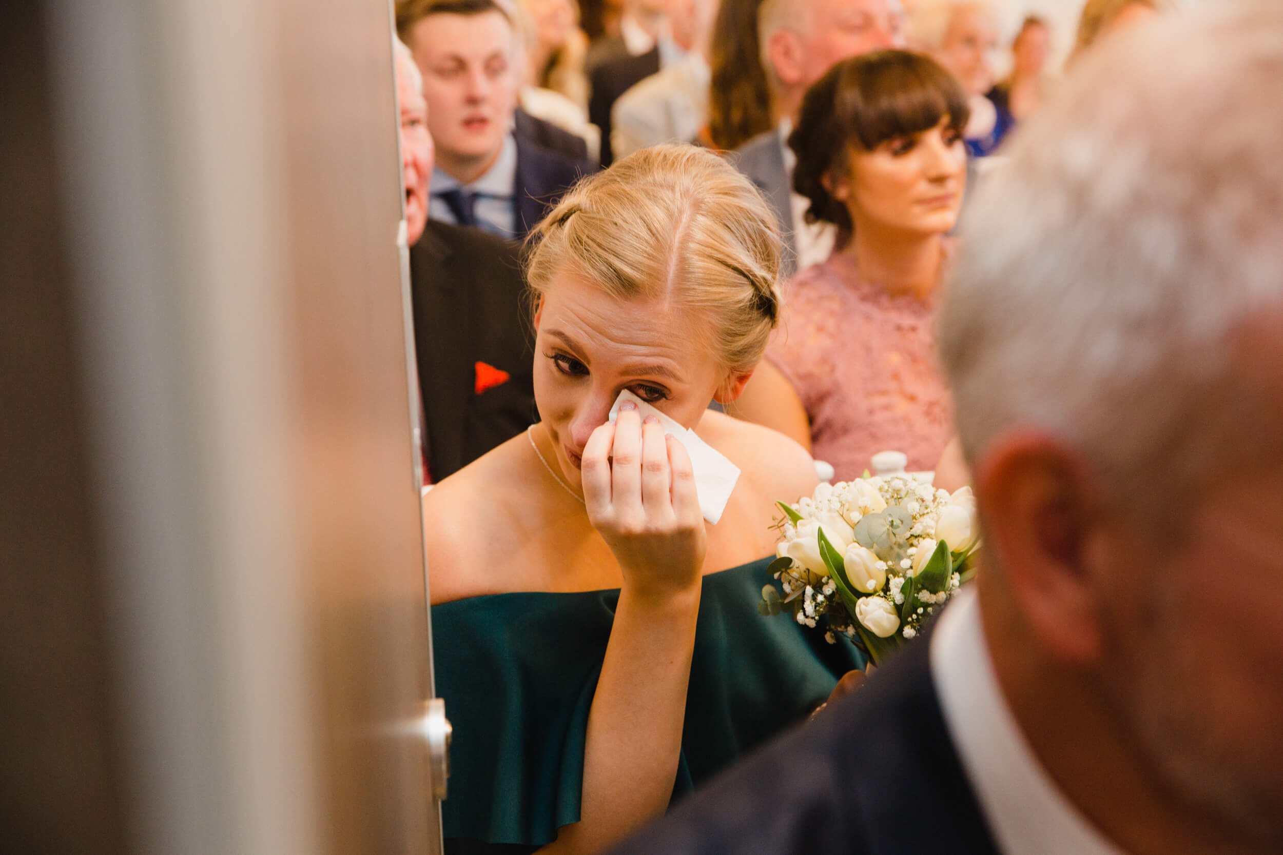 bridesmaid wiping away tear with tissue during vows at oddfellows on the park