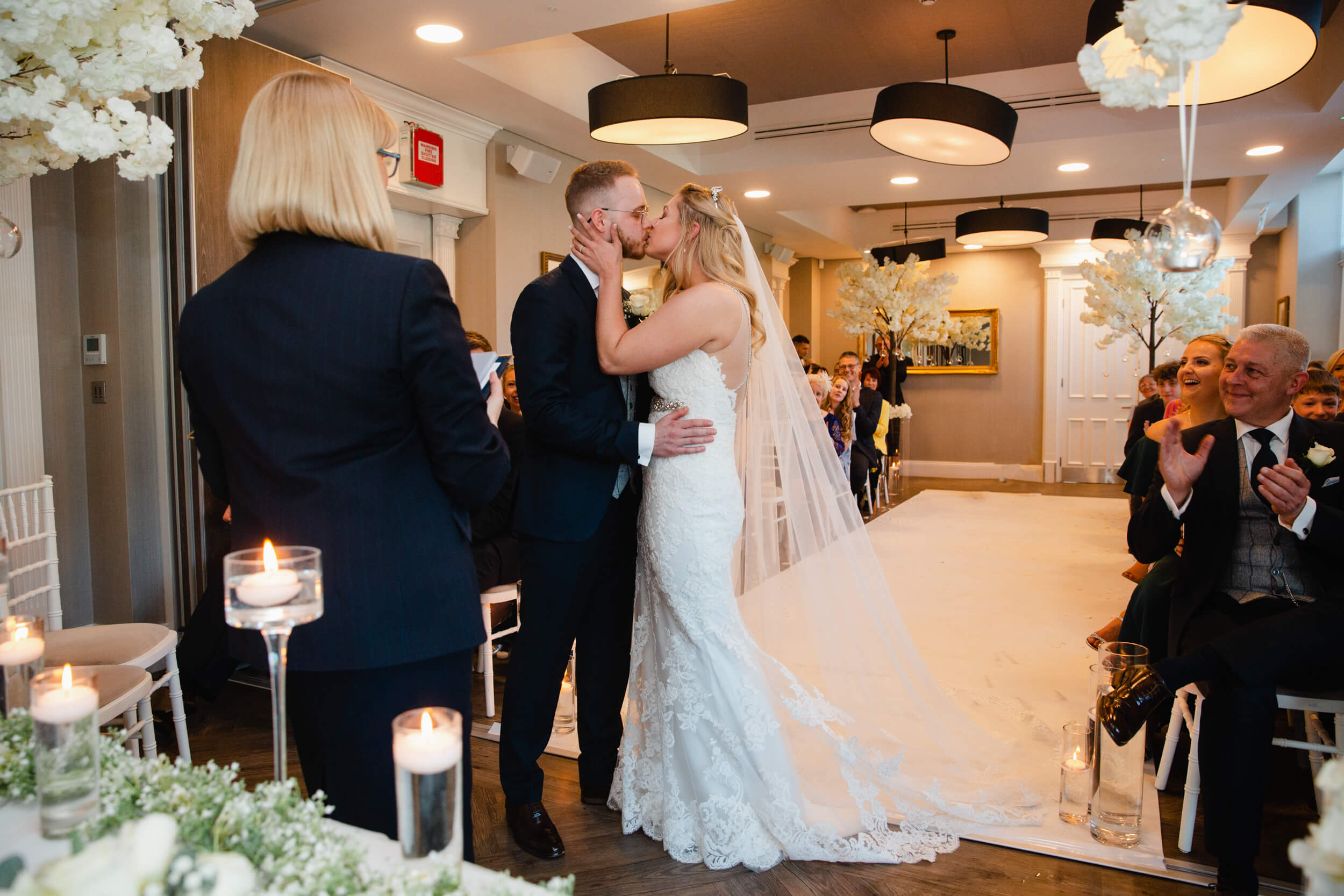 wide angle lens photograph of bride and groom first kiss