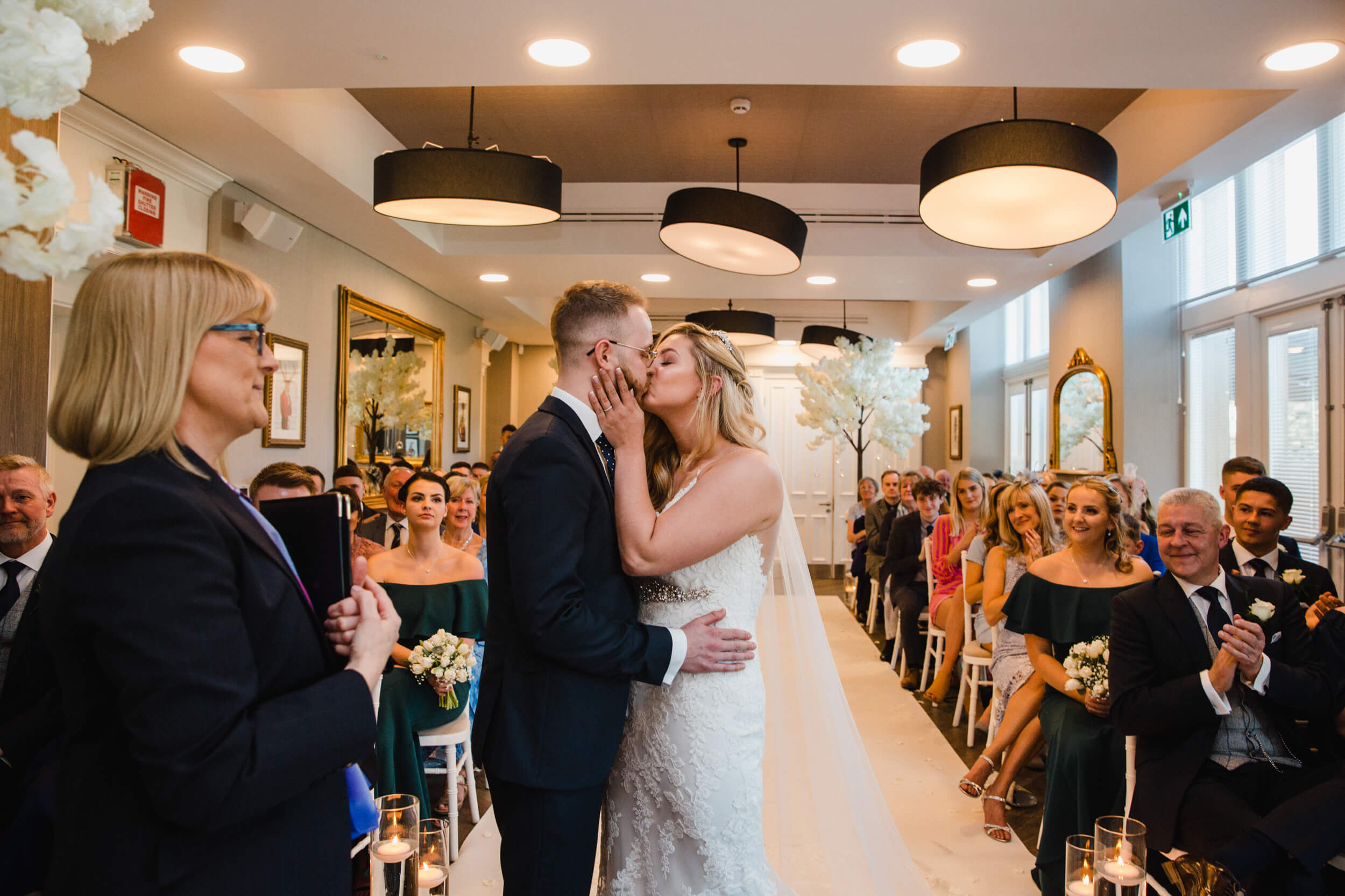bride and groom first kiss at top of aisle with family congratulating
