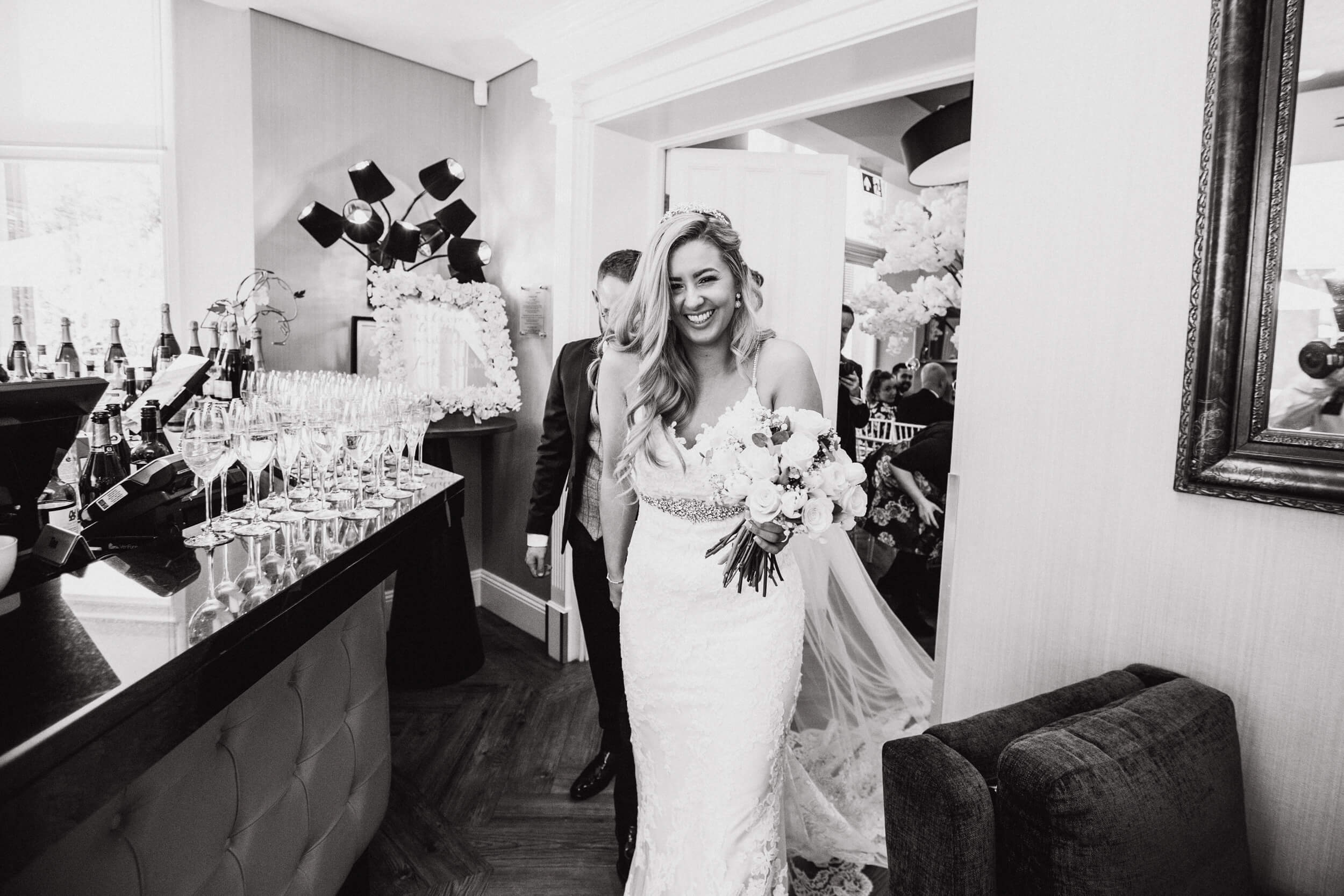 black and white photograph of bride smiling holding bouquet of flowers