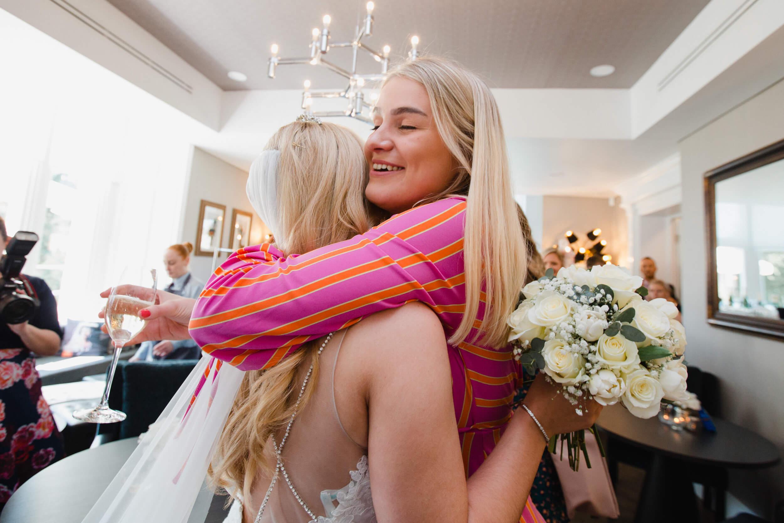 wedding guest hugs and congratulates bride