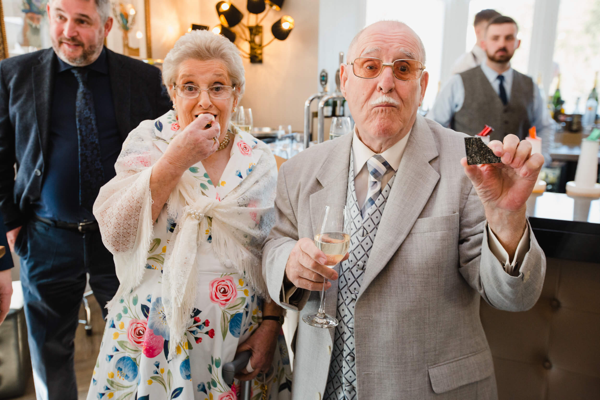 grandparents pose for camera while eating canapés
