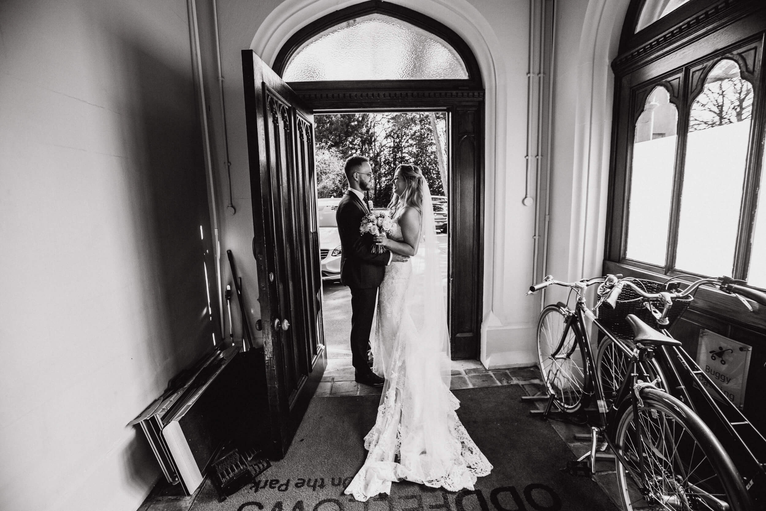 black and white portrait of newlyweds in doorway of oddfellows on the park
