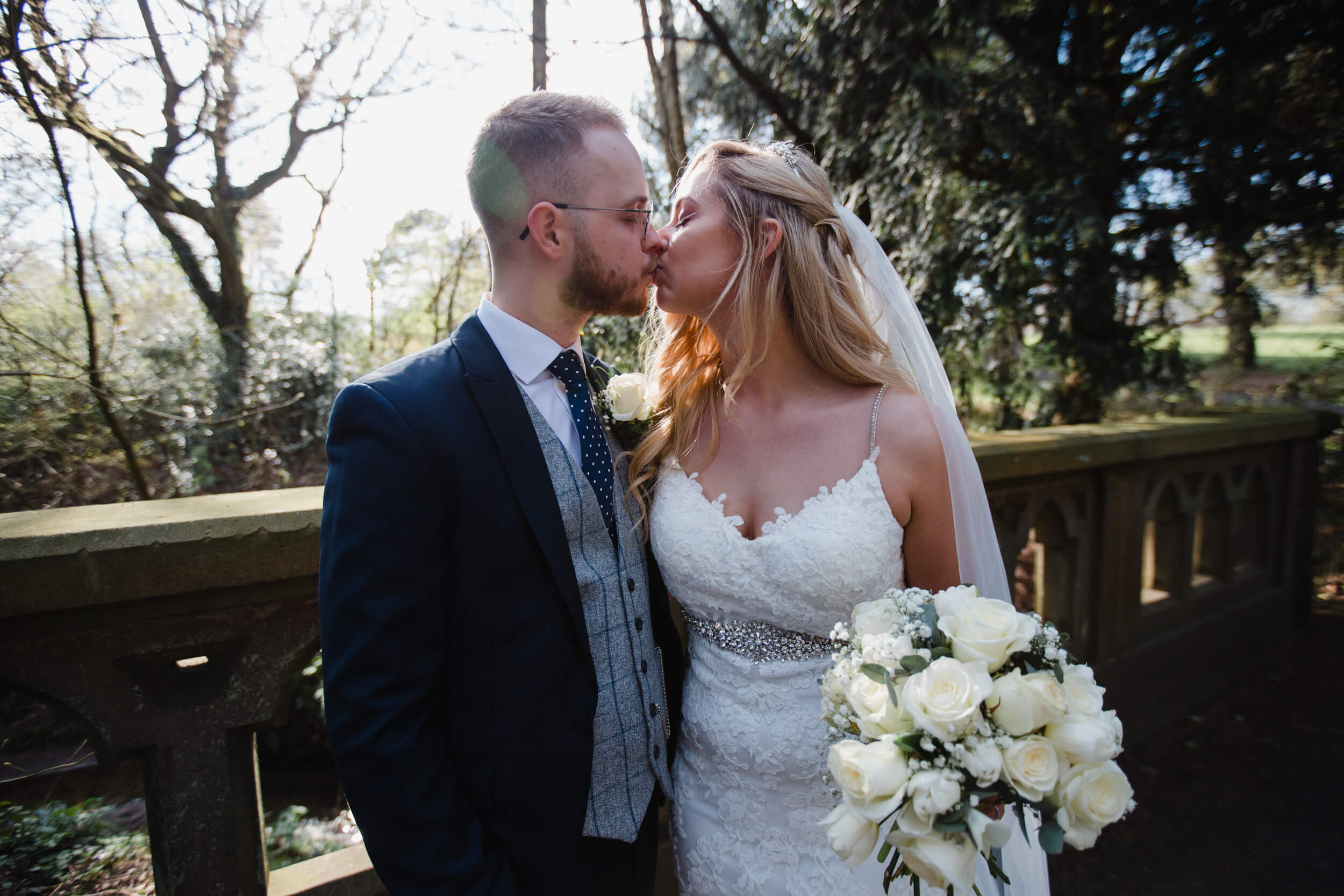close up photograph of bride and groom kissing by parkland