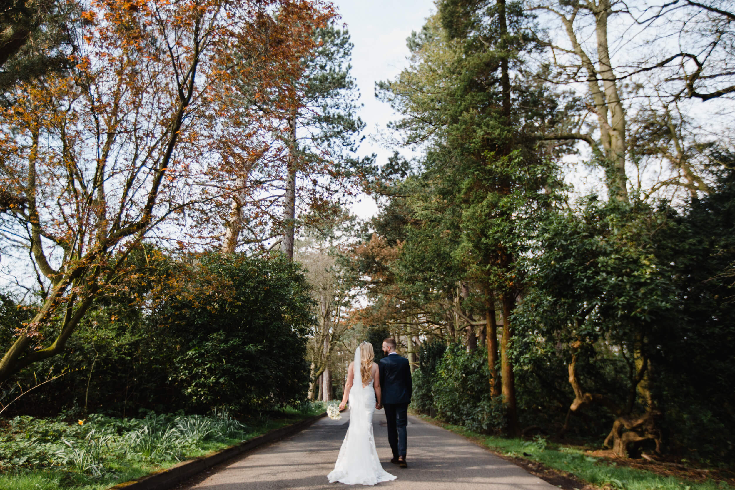 wide angle lens photograph of newlyweds holding hands between trees at the park