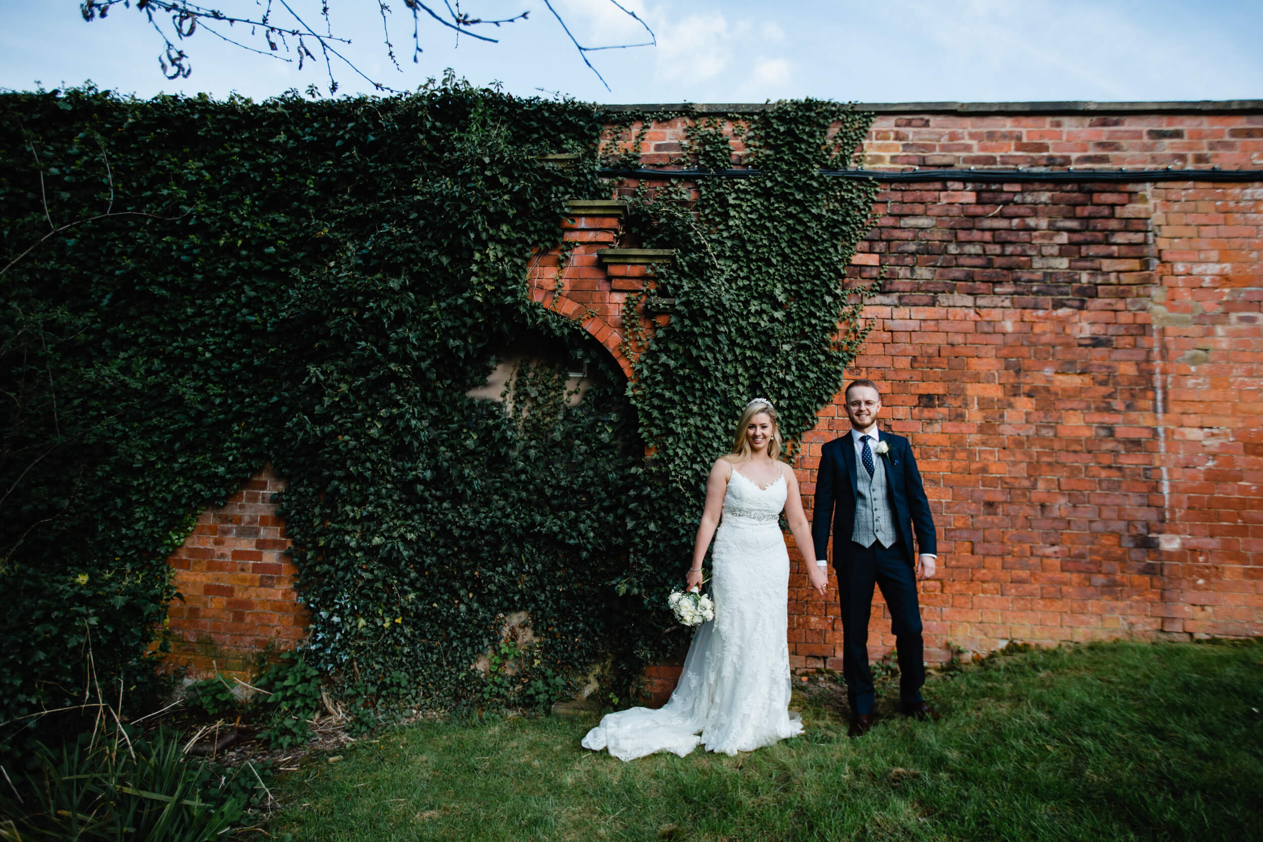 bride and groom holding hands against red brick ballpark wall