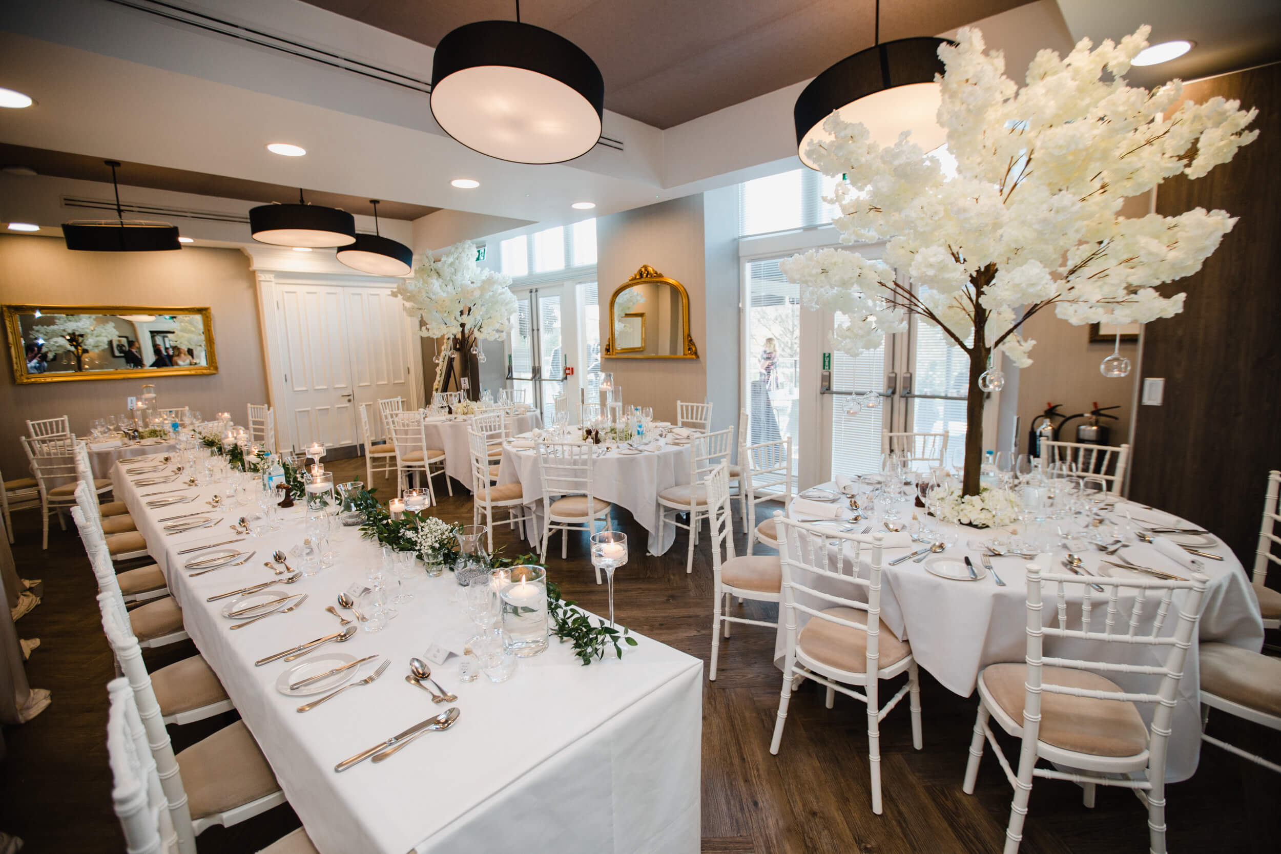 wide angle lens photograph of wedding breakfast room with blossom tree tables