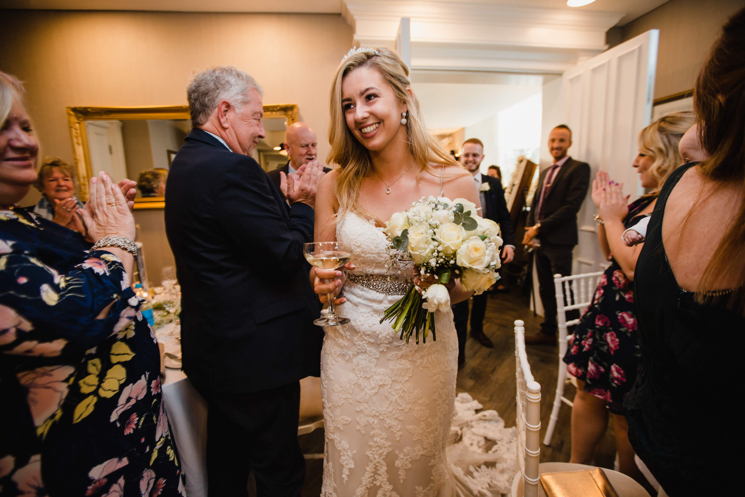 smiling bride holding champagne and bouquet entering wedding breakfast room