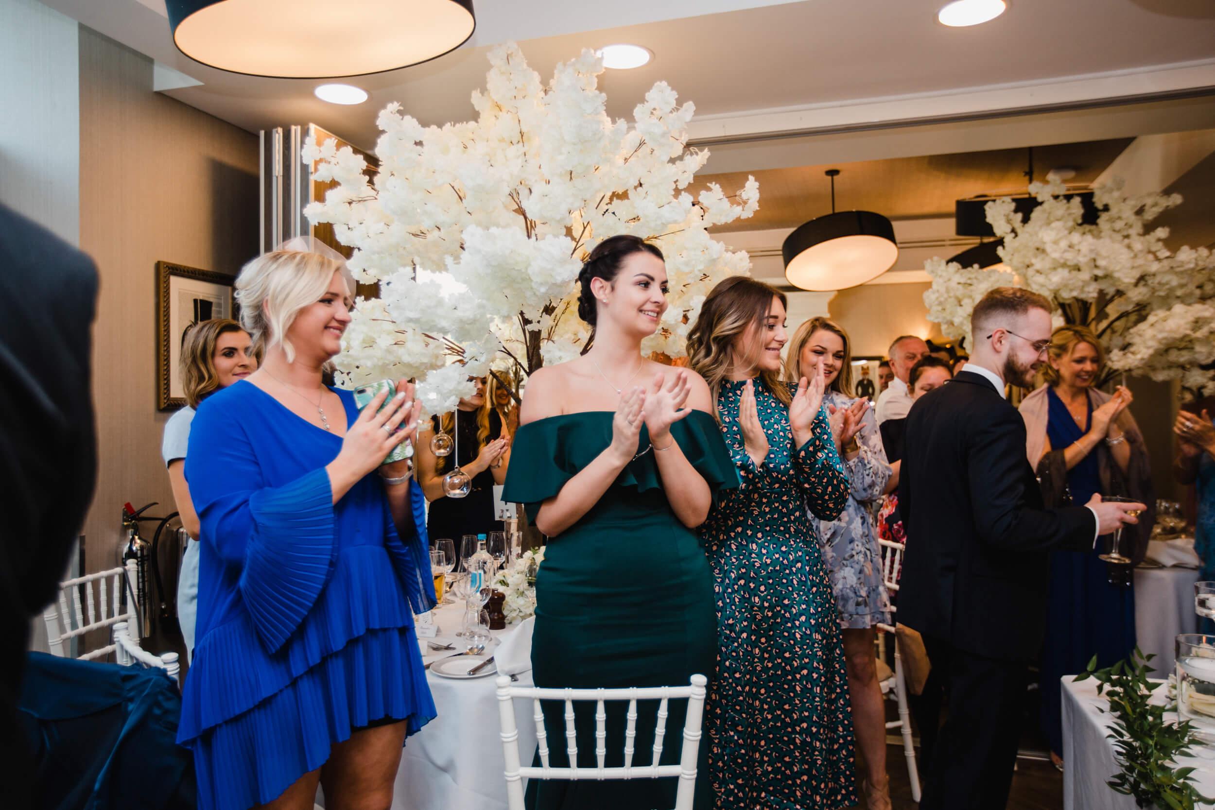 wedding guests and bridesmaids cheering entrance of newlyweds