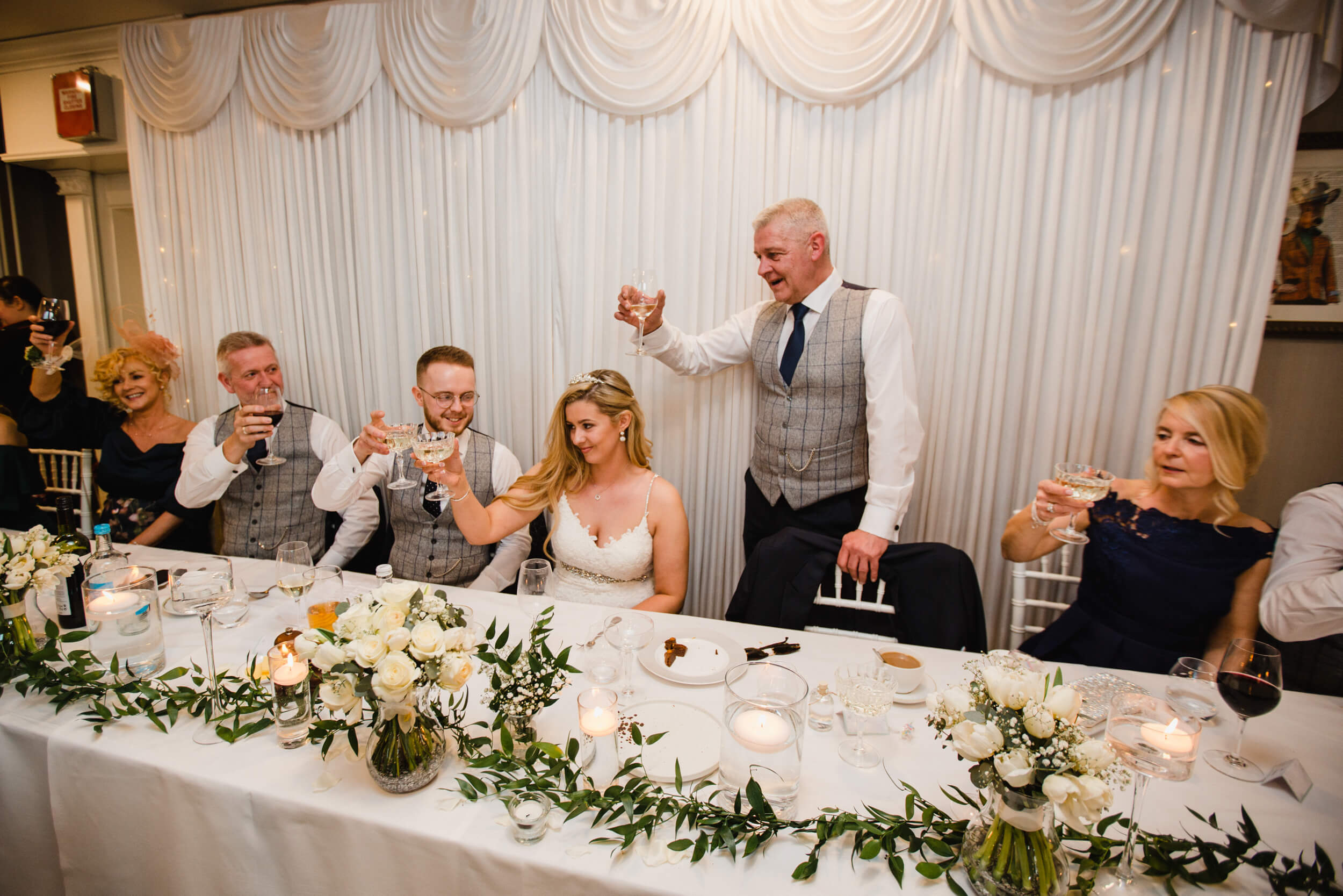 father of bride raising a toast to newlyweds during speeches