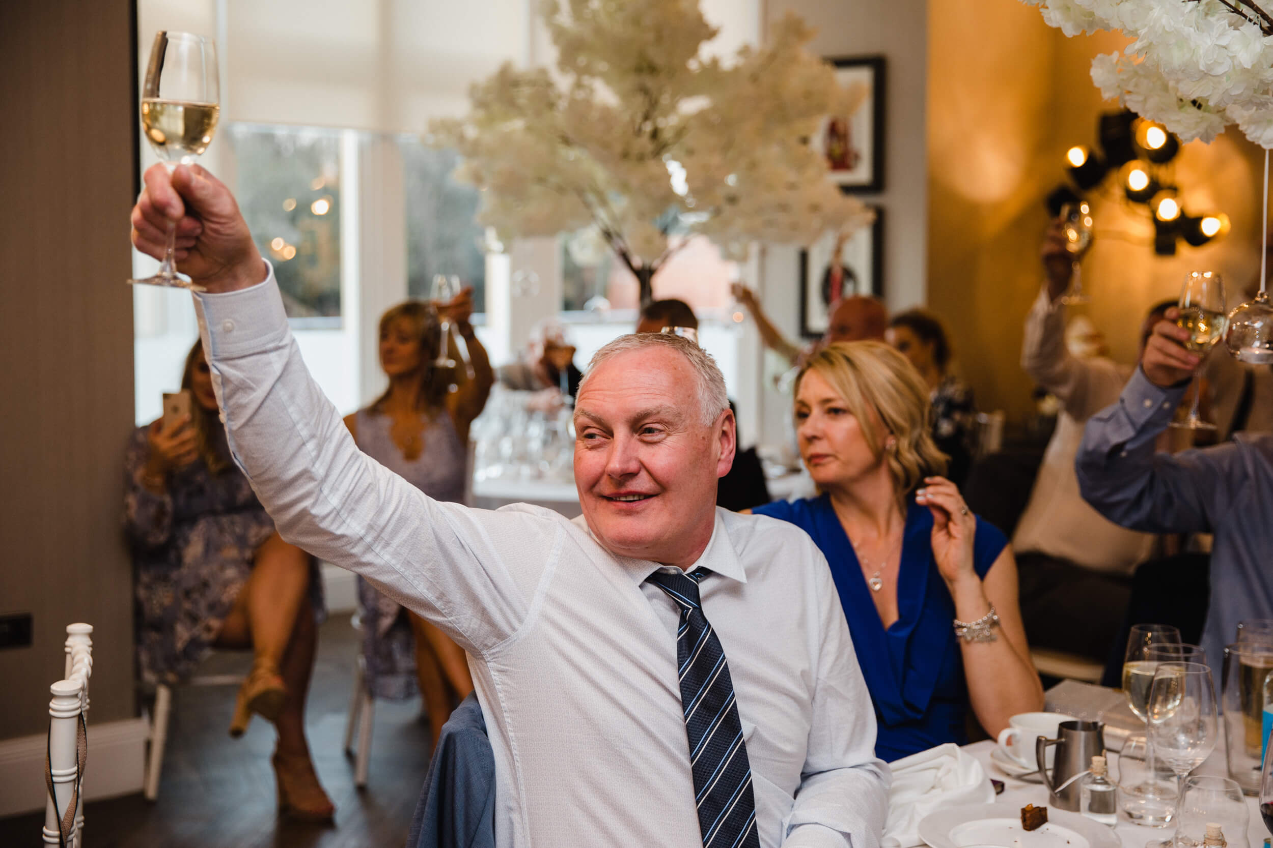 close up photograph of wedding guest holding glass of champagne