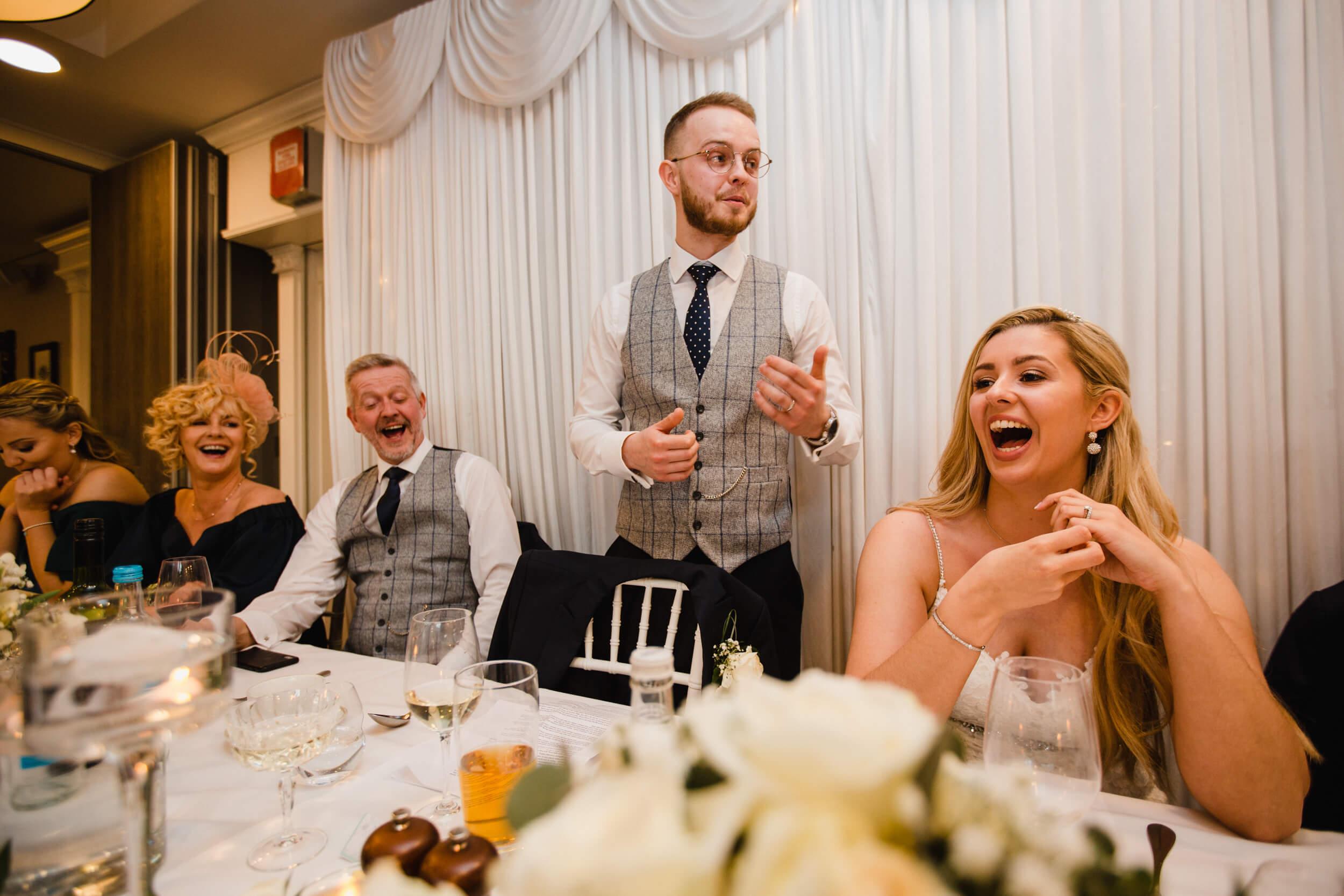 groom delivering speech to wedding party with top table reactions and laughter