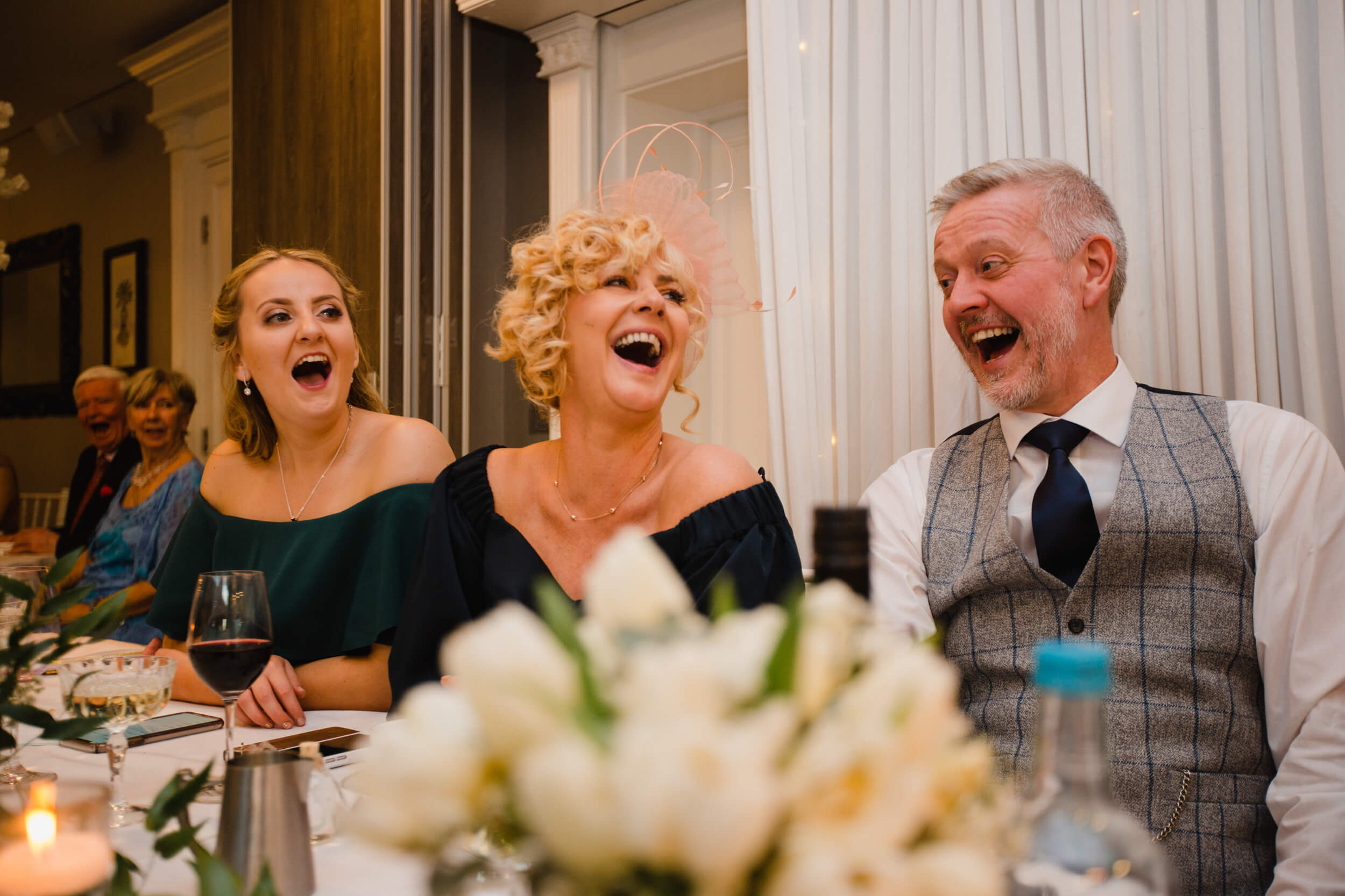 bridal party laughter on top table to grooms speech