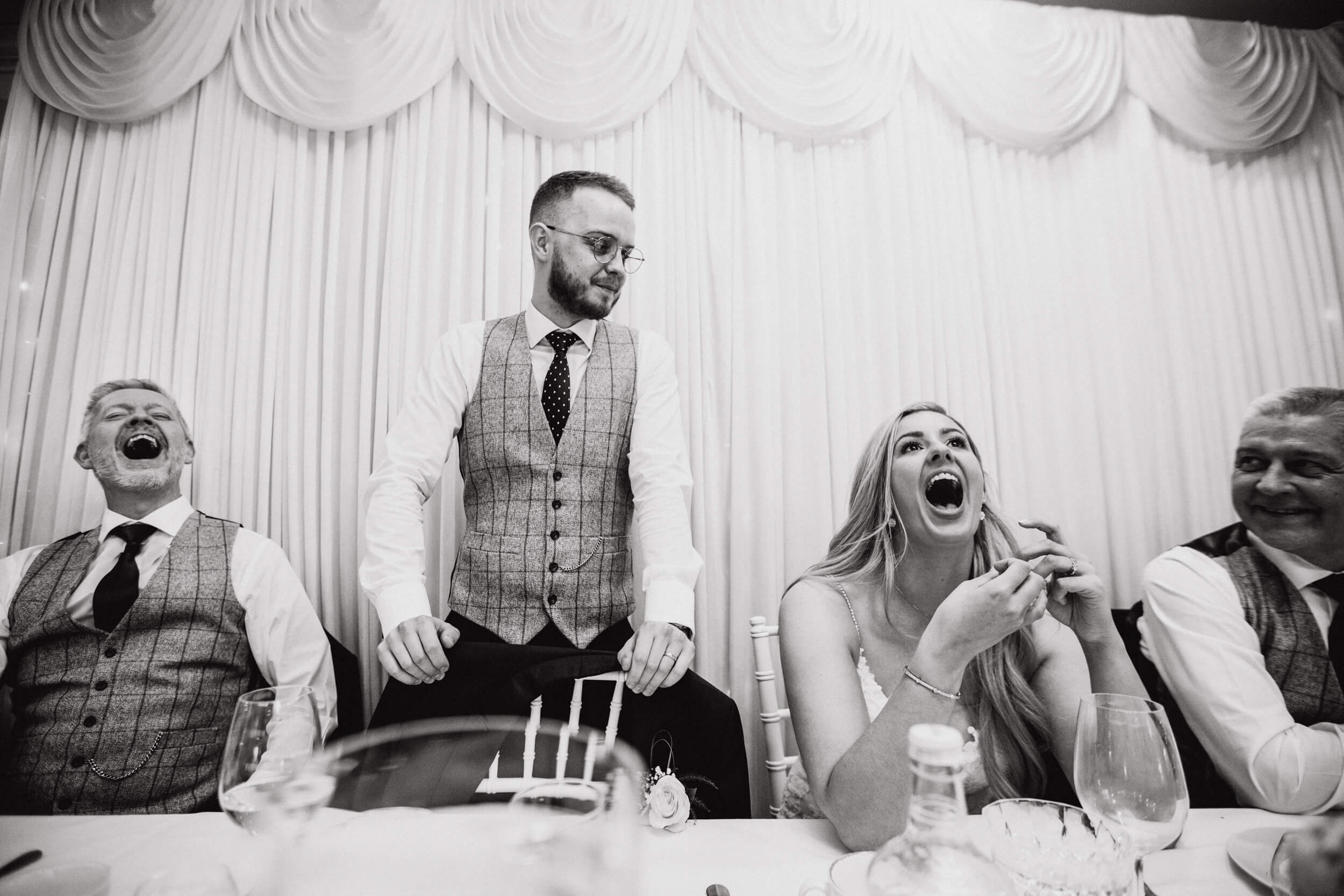 black and white close up photograph of groom delivering speech to wedding party