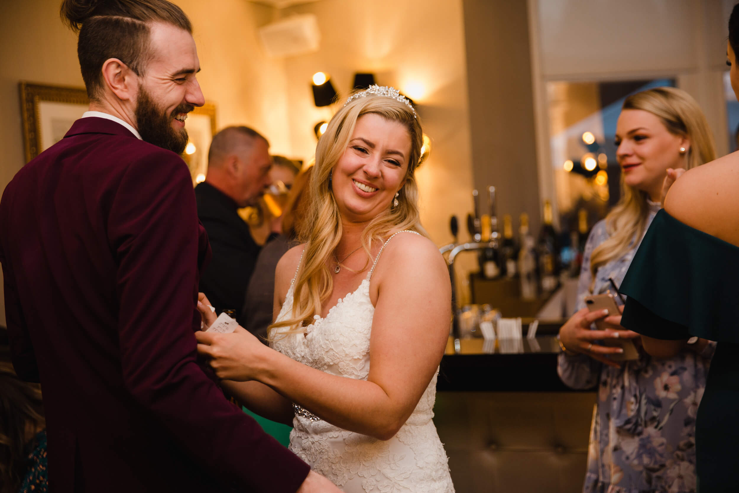 bride laughing and sharing joke with friend on dance floor