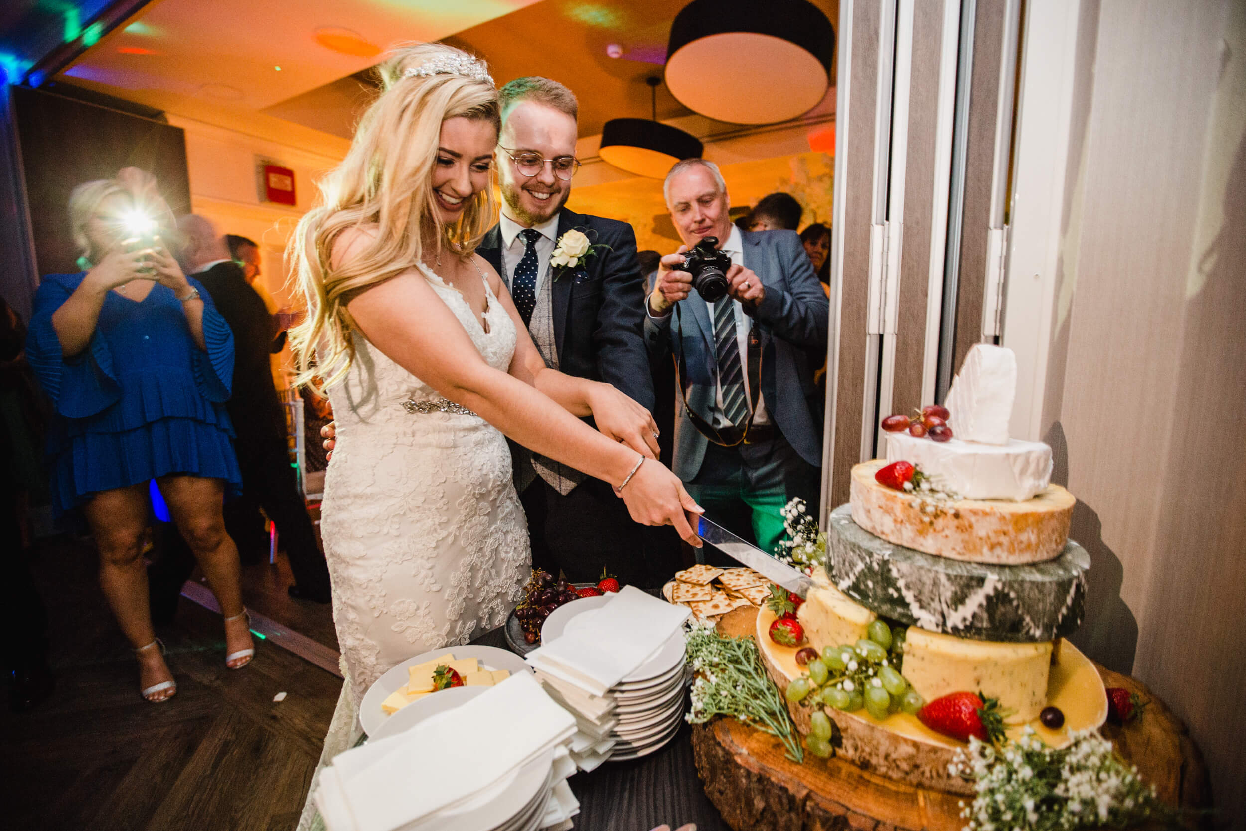 bride and groom cut wedding cake with family and friends