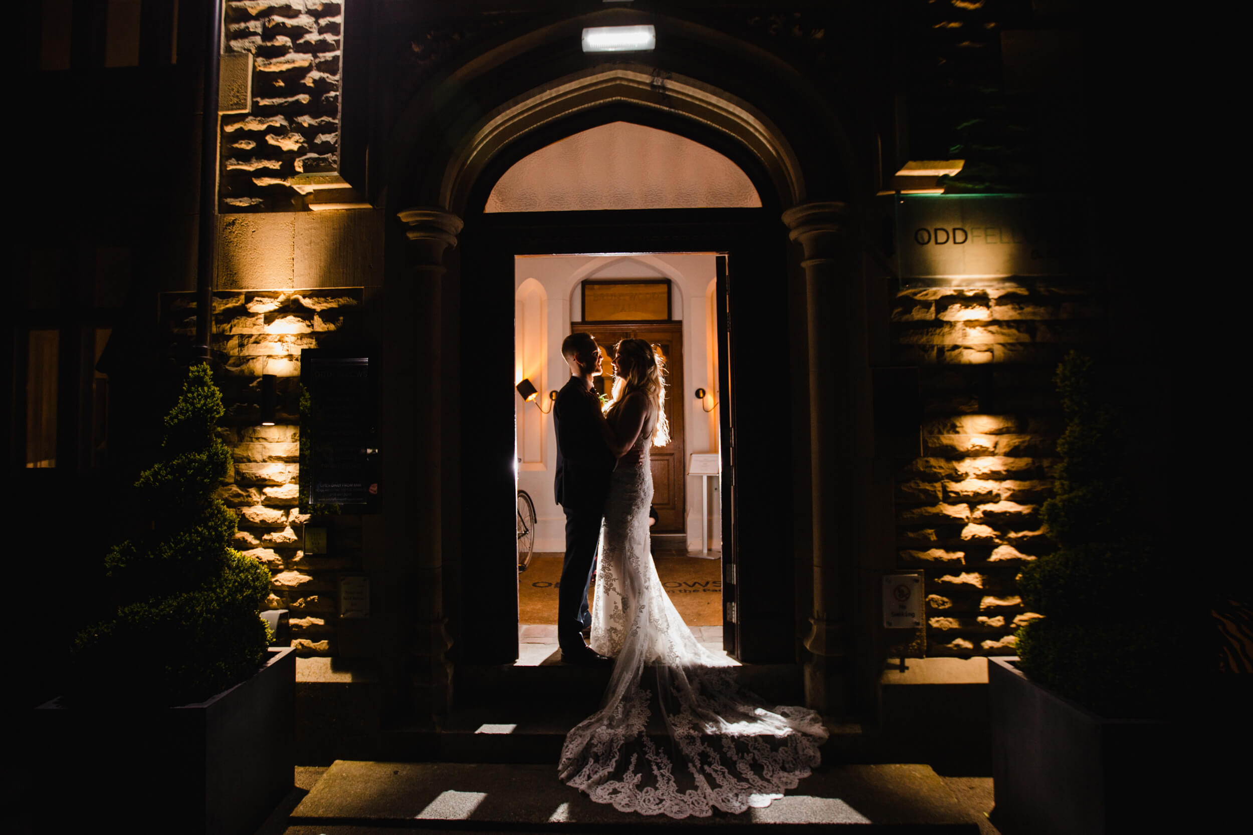 night exposure photograph using flash to light wedded couple in doorway of oddfellows on the park