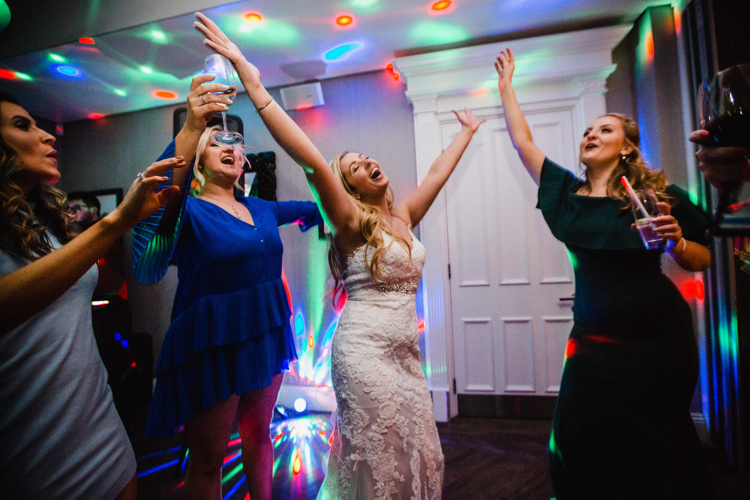 bride and bridal party dancing and holding arms in air at end of night