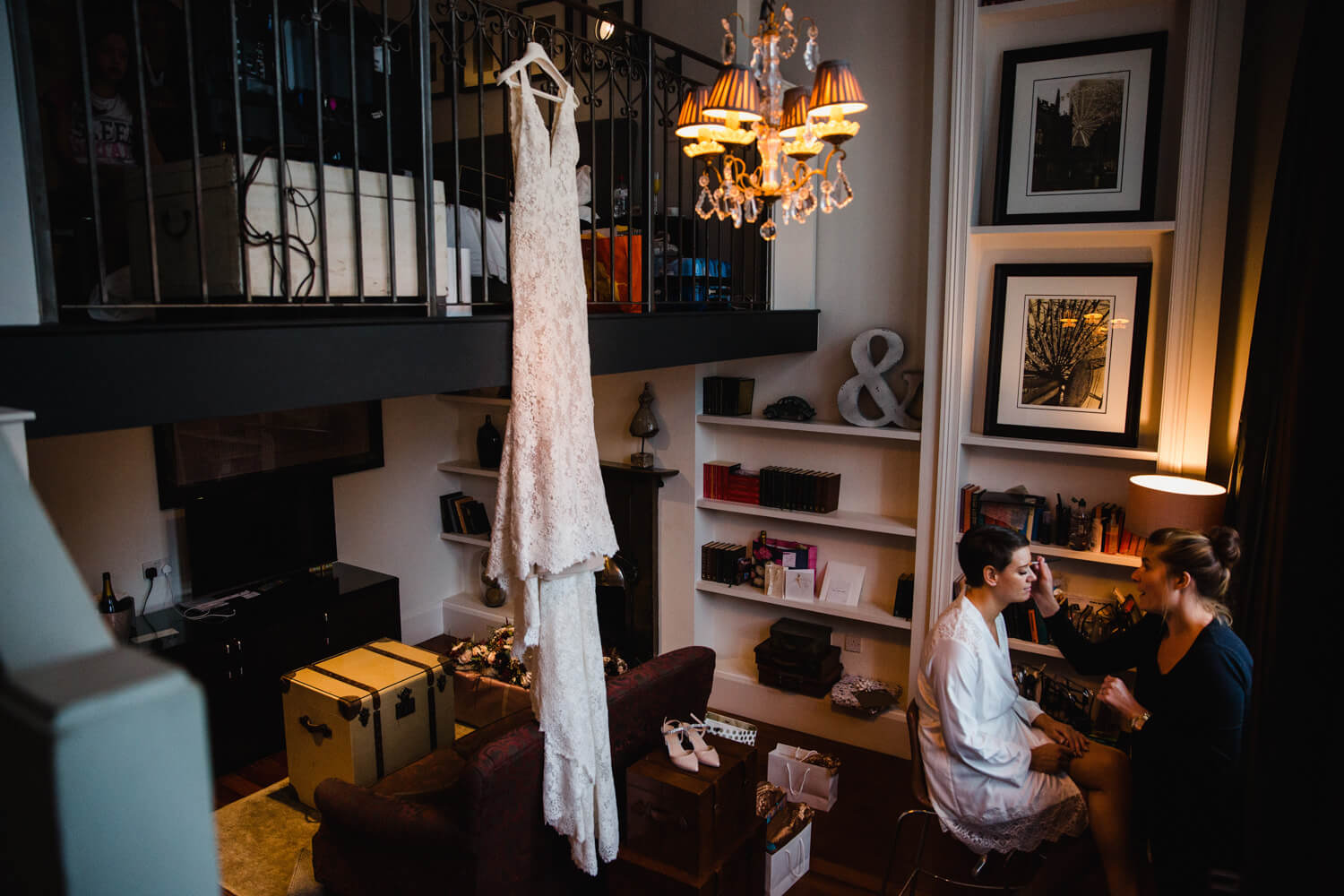 wedding dress hung from bannister while bride has make up applied in bridal suite at great john street hotel