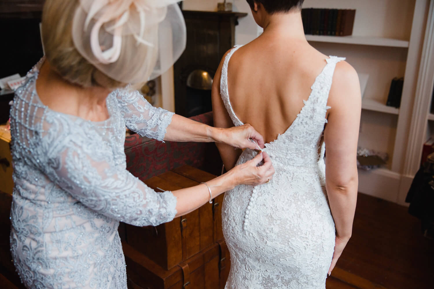 bride having wedding dress buttoned by mother