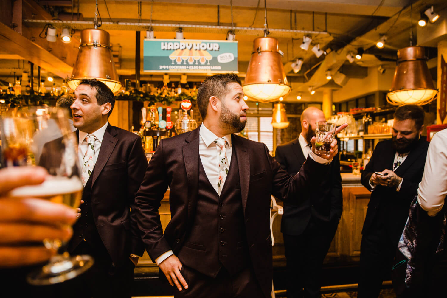 groom at the bar with groomsmen posing for photograph