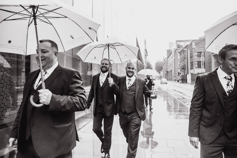 black and white photograph of groomsmen walking to wedding ceremony in rain