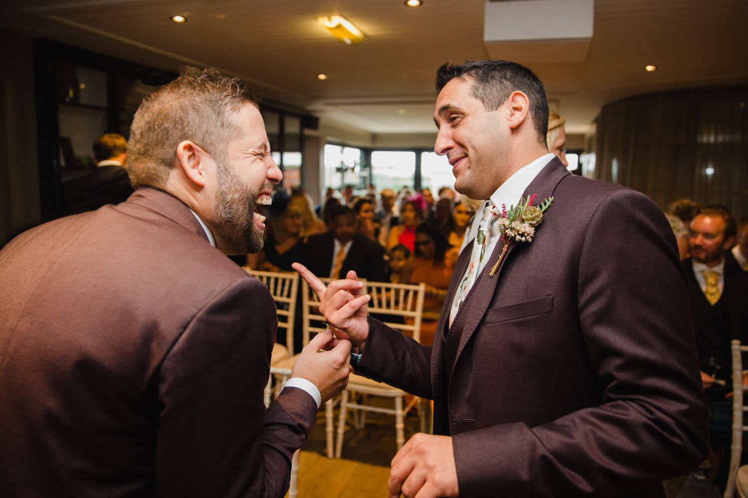 groom sharing joke with best man at the top of the aisle before wedding service