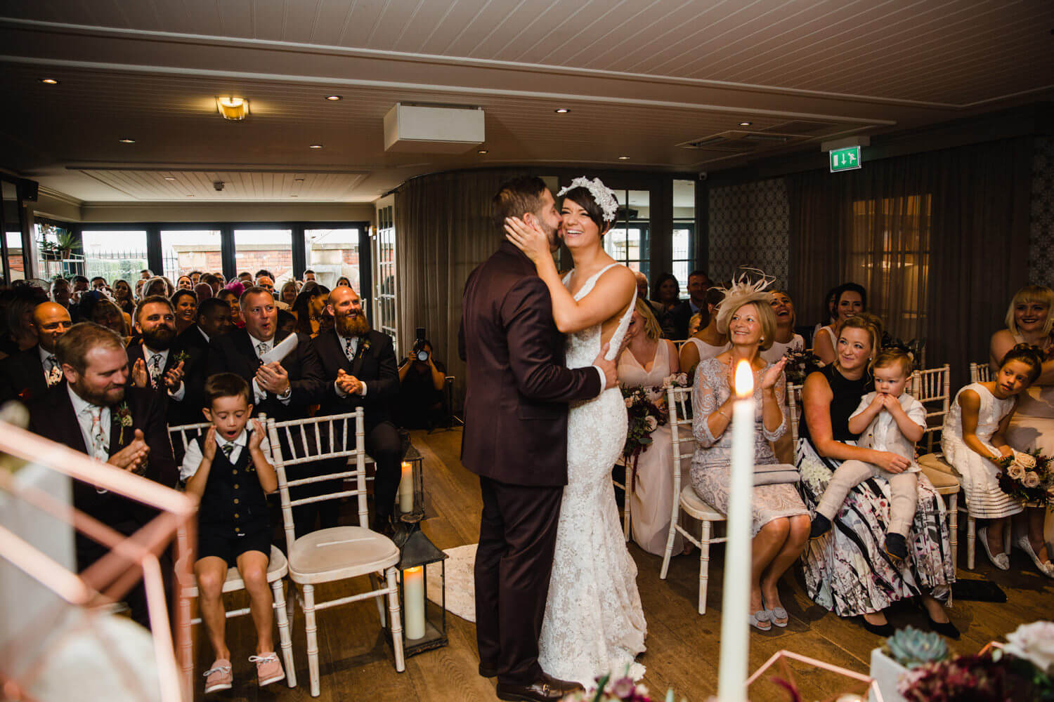newlyweds share first kiss while being congratulated by wedding party at great john street hotel
