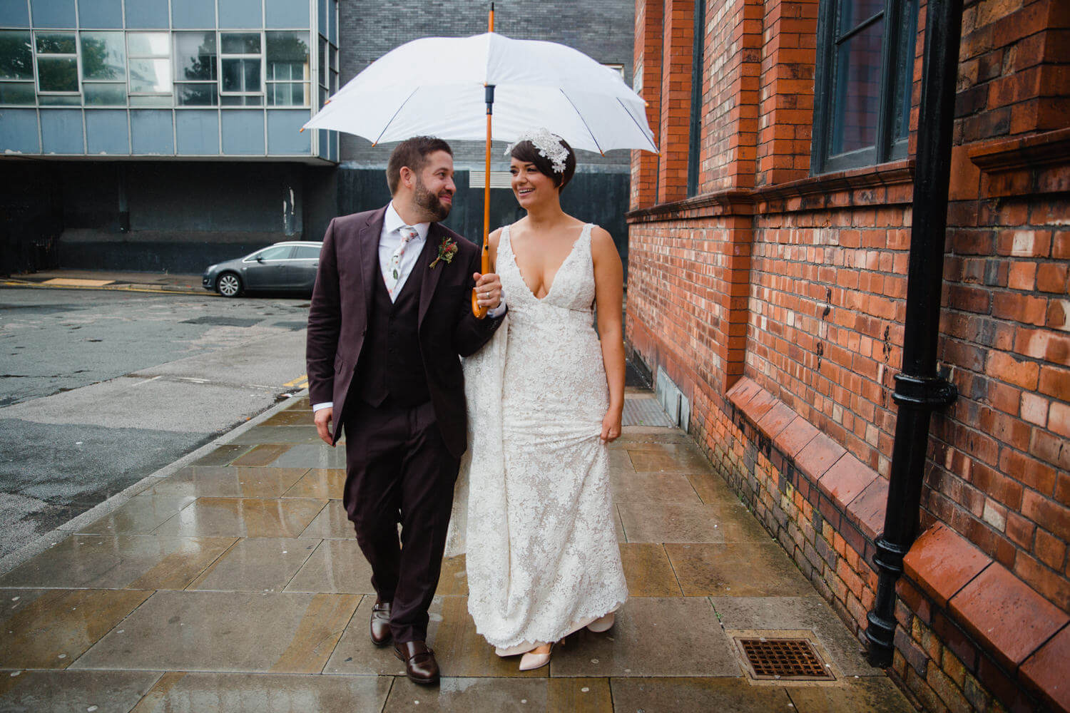 newlyweds walk down pavement for posed portrait next to alley towards camera holding umbrella