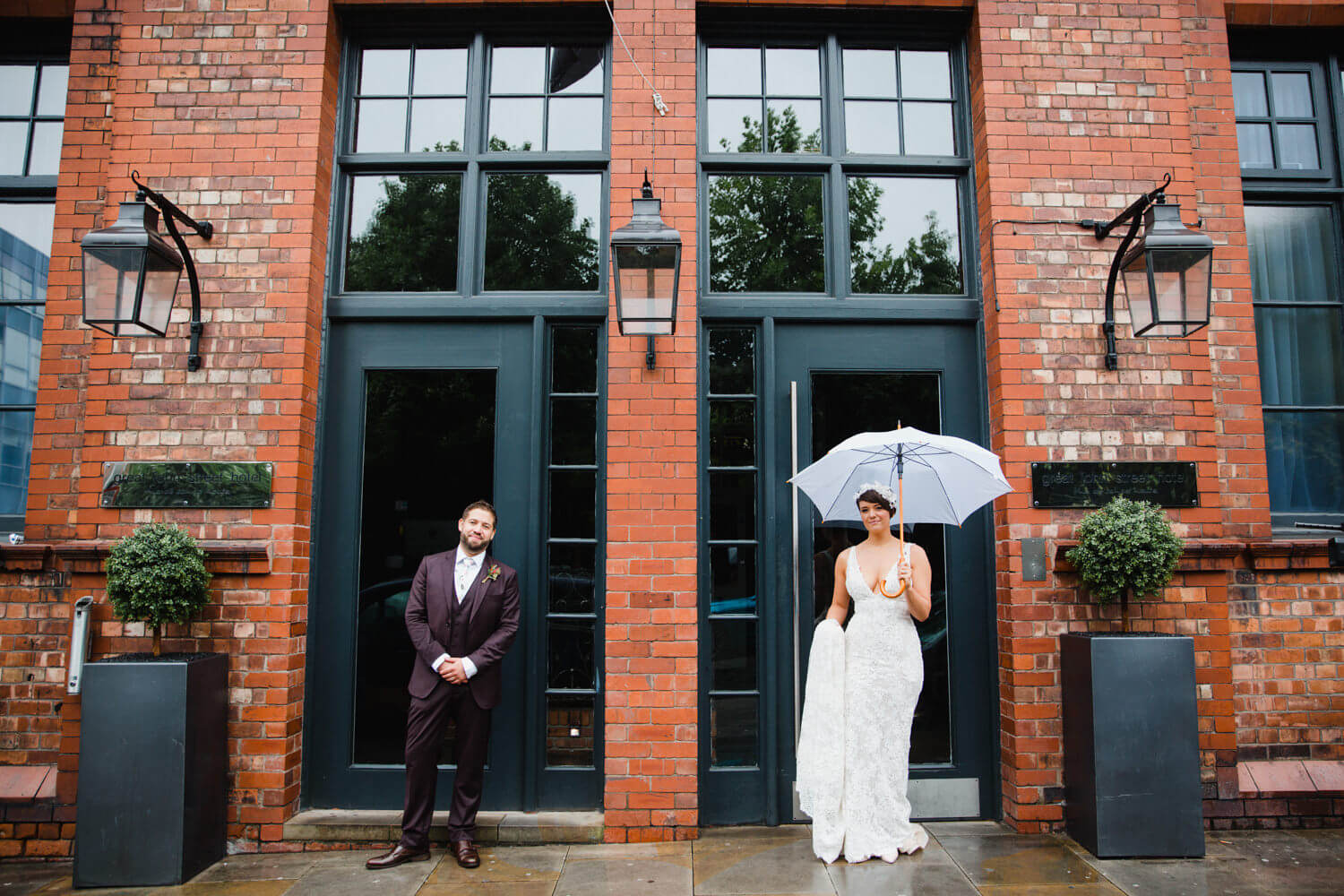 bride and groom stood in doorway for posed portrait at great john street hotel wedding photography