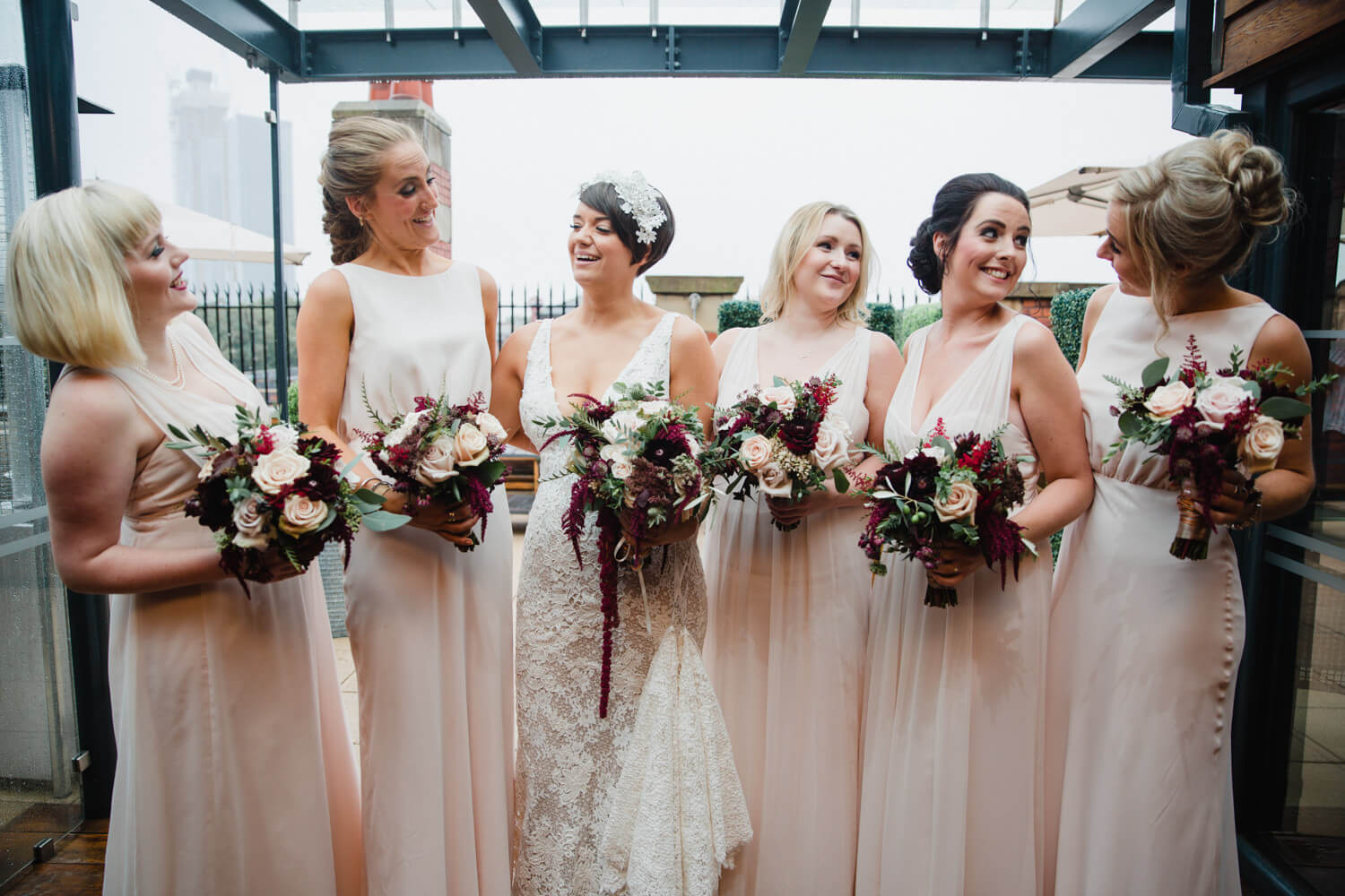 bridesmaids all holding bouquets while looking at camera for great john street hotel group photograph