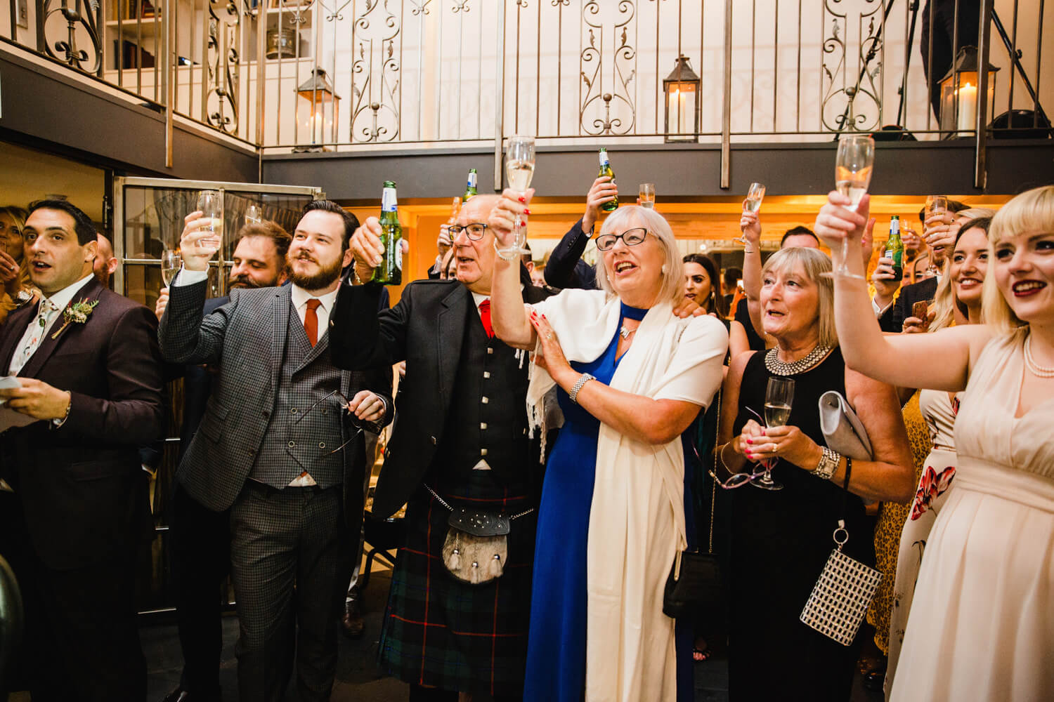 wedding party raising a toast to newly married couple after speeches