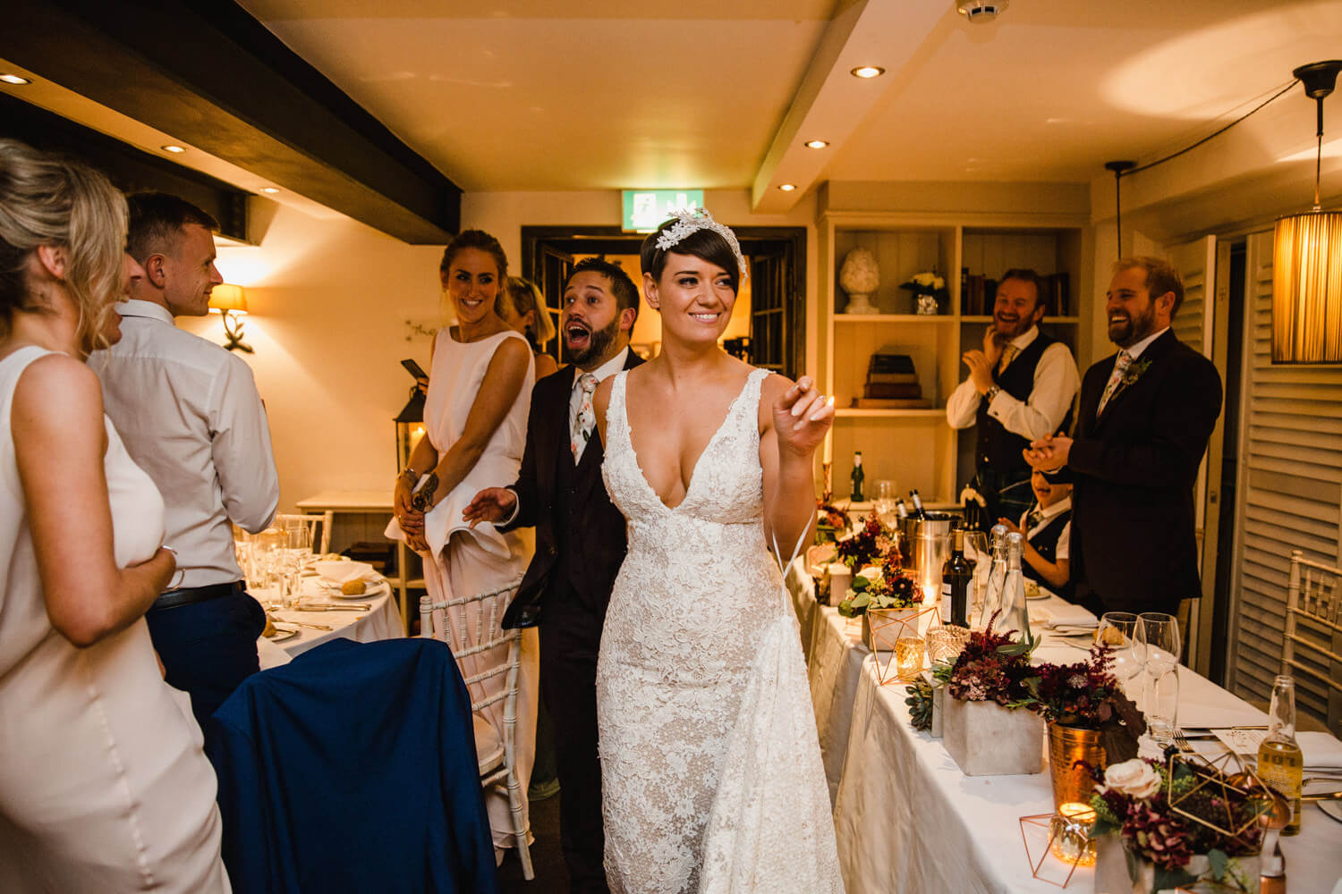bride and groom enter the room after nuptials to be seated at top table