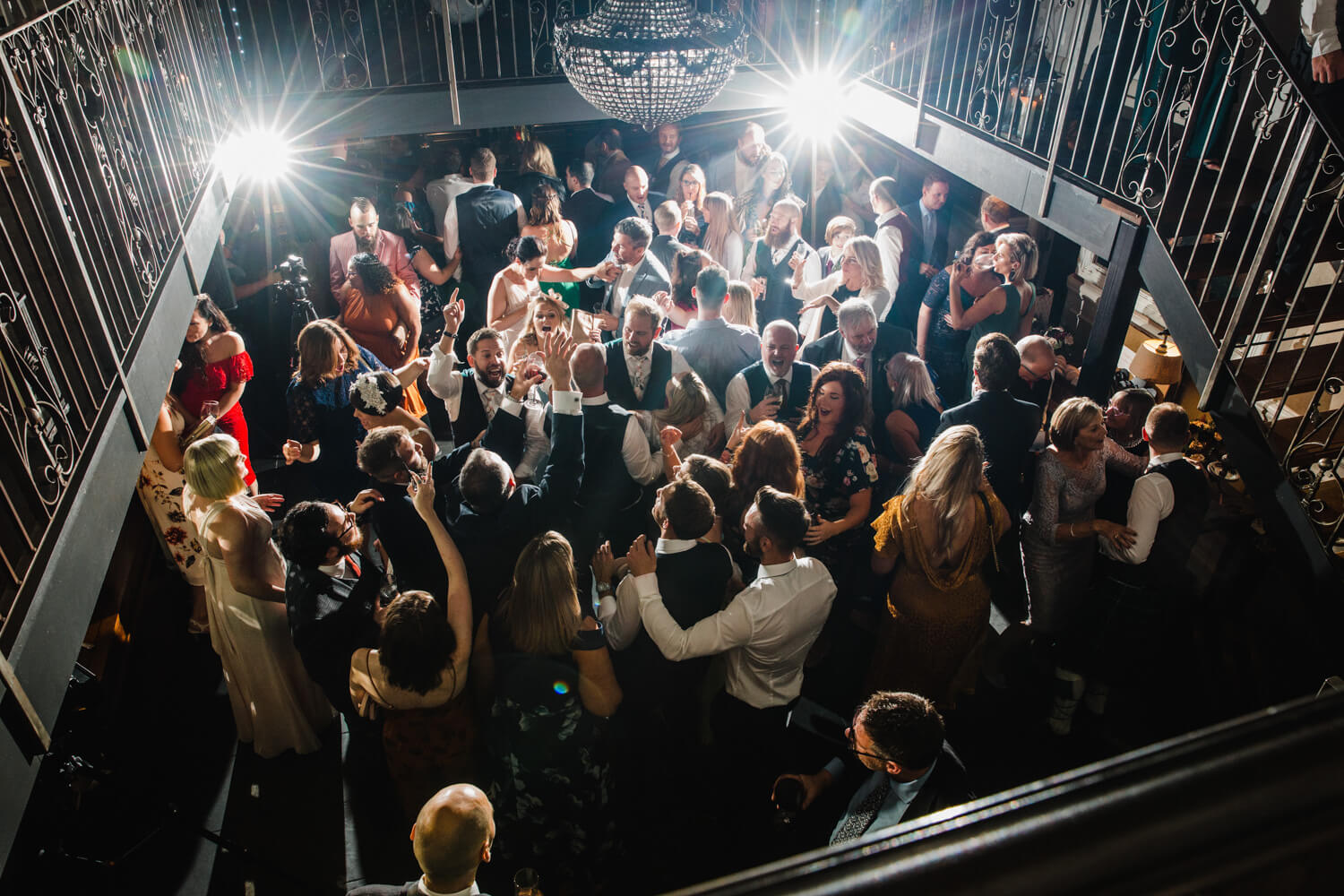 filled dance floor lit by flash starlights as wedding party celebrate