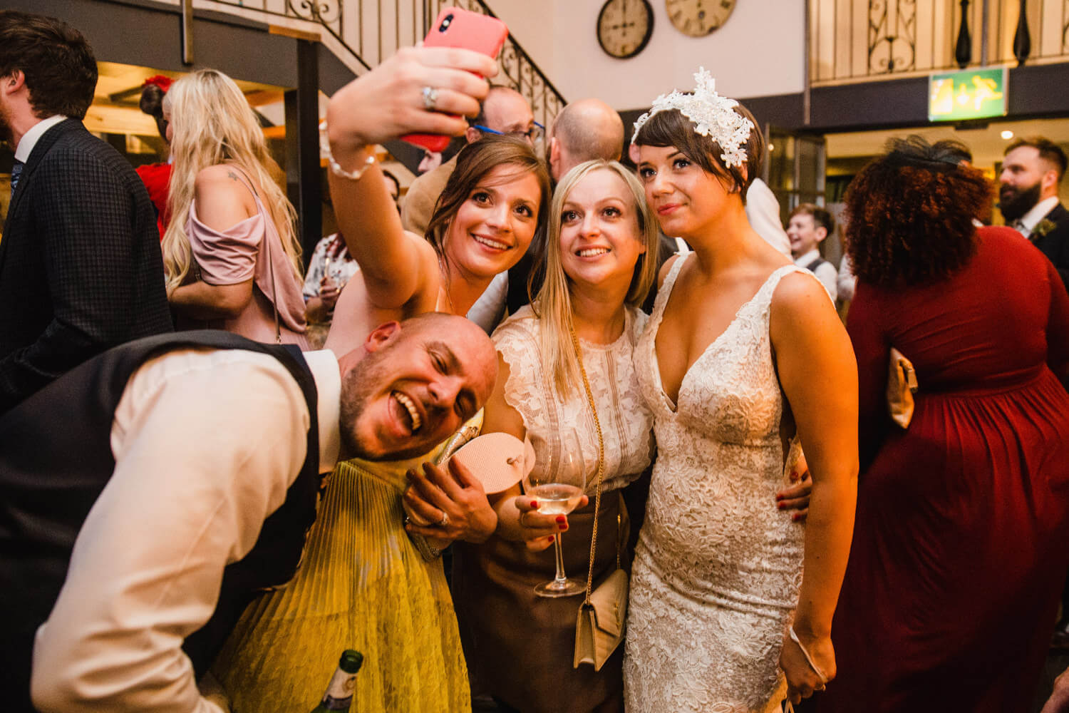 bride and guests enjoying camera phone photograph together on dance floor