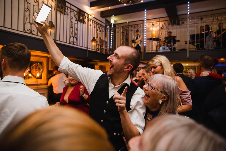 wedding guests taking phone camera selfies
