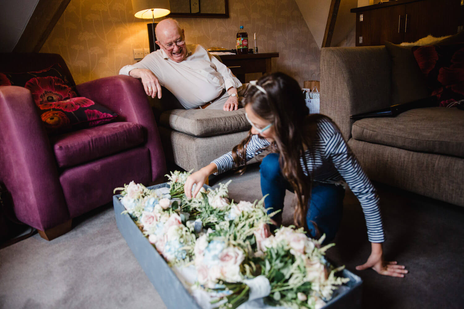 photograph in dining room of grandfather watching flower lounge girl arrange bouquets