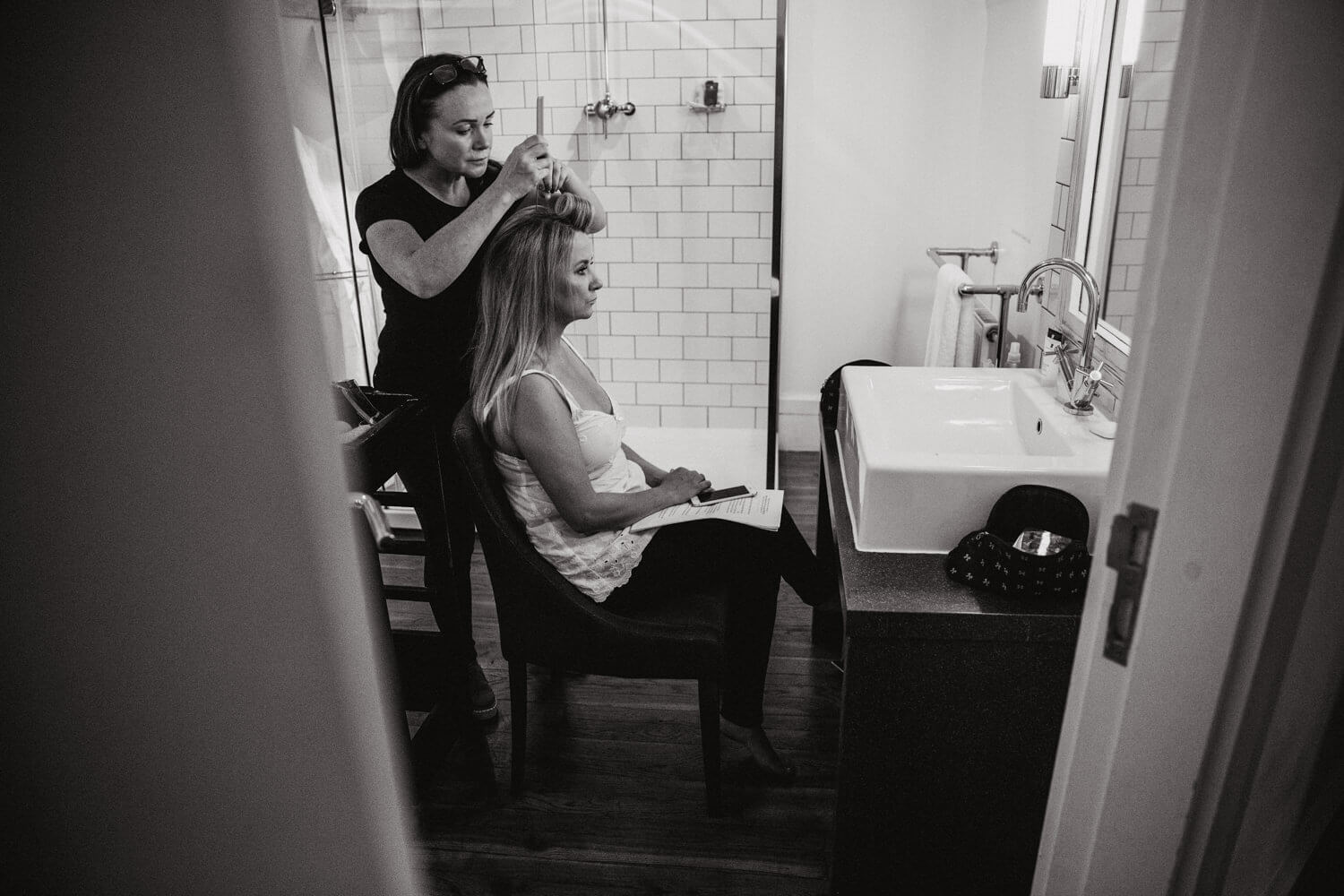 black and white photograph of bride having hair styled before ceremony