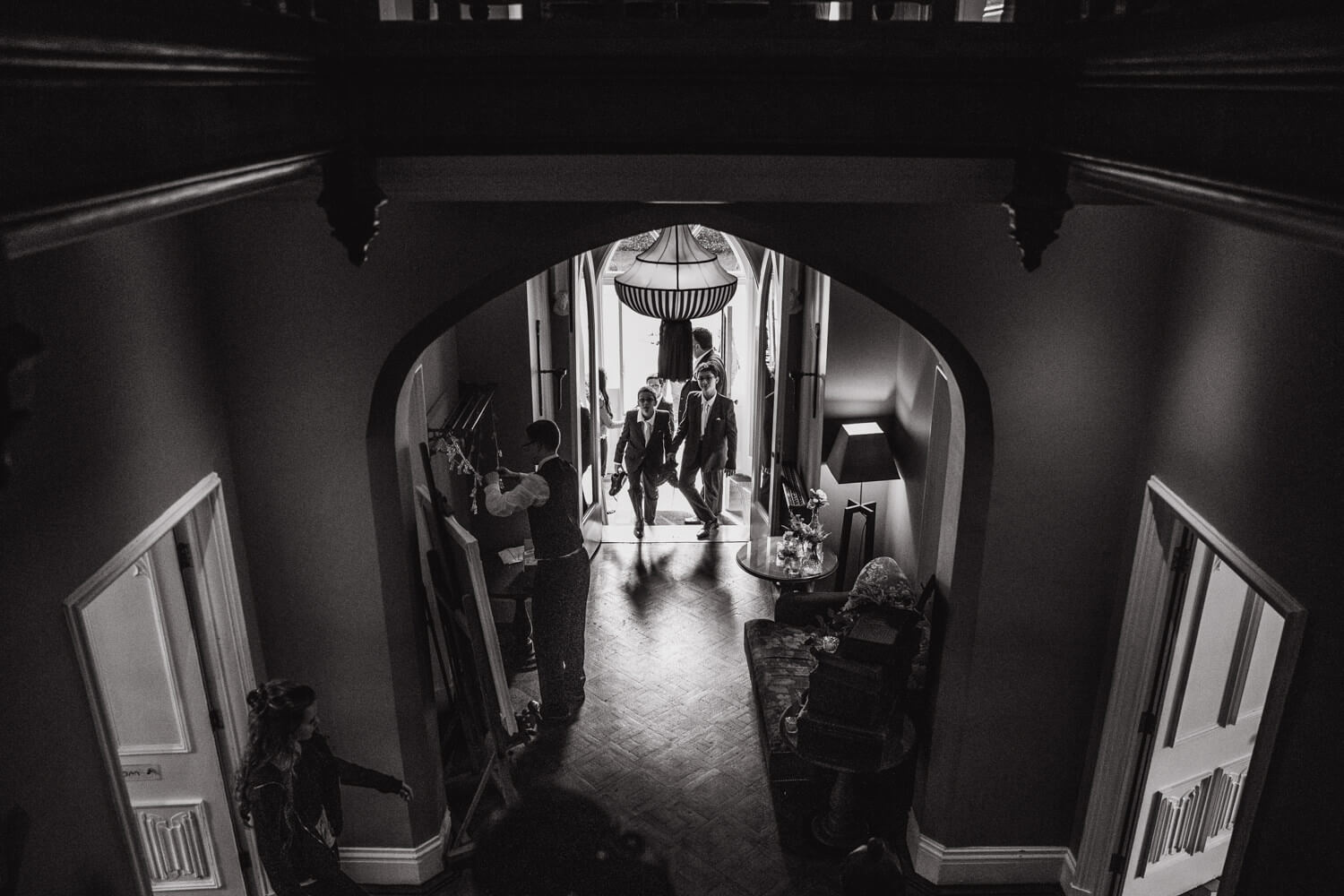 black and white photograph taken from staircase with groomsmen entering hallway at didsbury house hotel