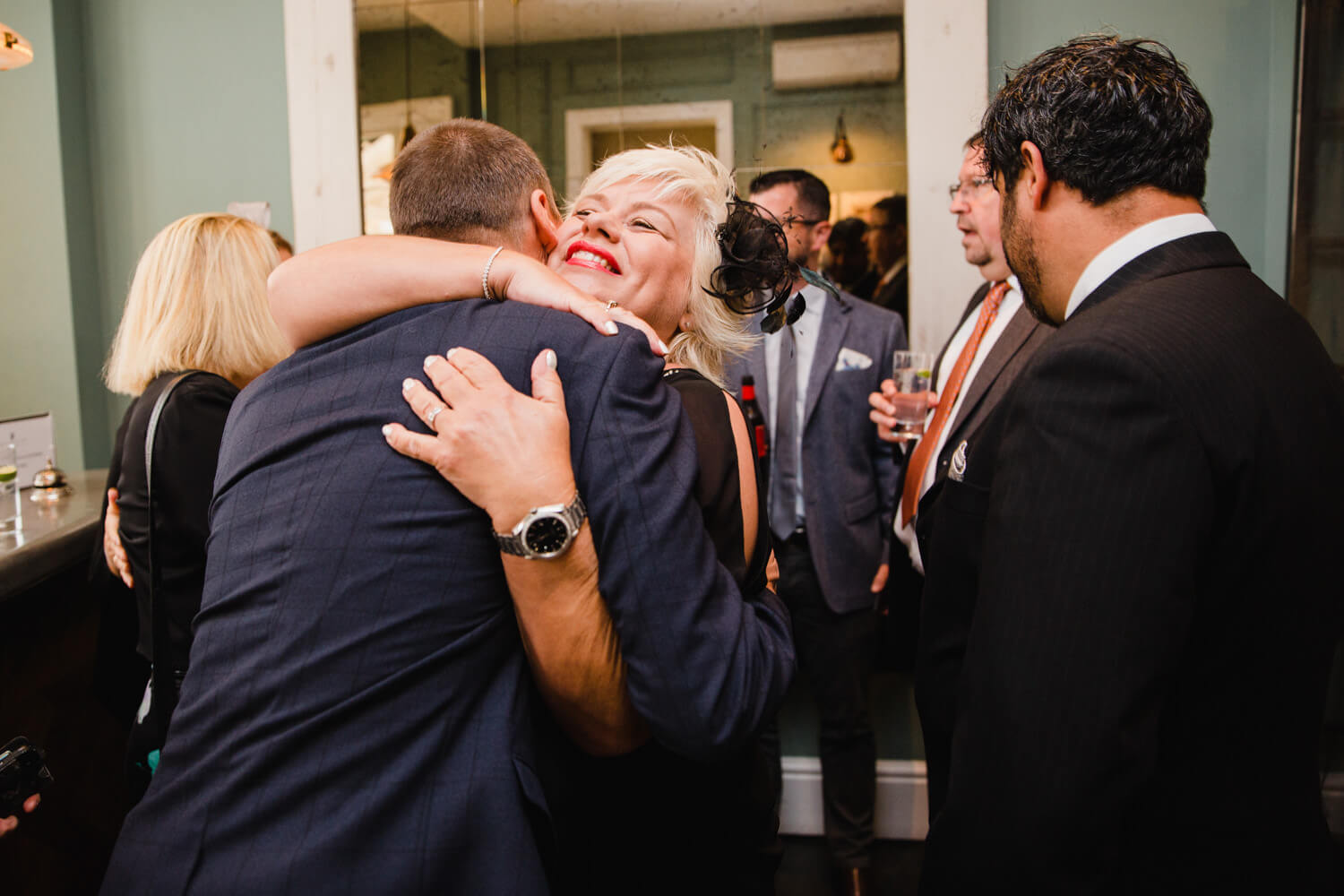 wedding guest hugs groom in lobby before ceremony